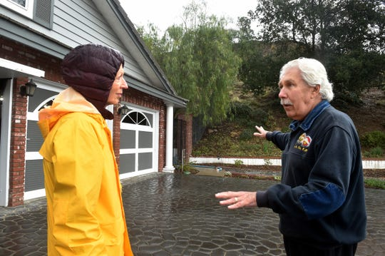 Pitt Gilmore, right, a retired Los Angeles County Fire Department captain, speaks with neighbor Diane Starzak about the possibility of debris flows in their Oak Park neighborhood as the rain began to fall for a second day on Tuesday. The neighborhood is surrounded by hills that were burned in the recent Woolsey Fire.
