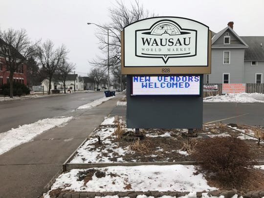 A sign for the Wausau World Market on 3rd Avenue, near the entrance and exit to the parking lot.