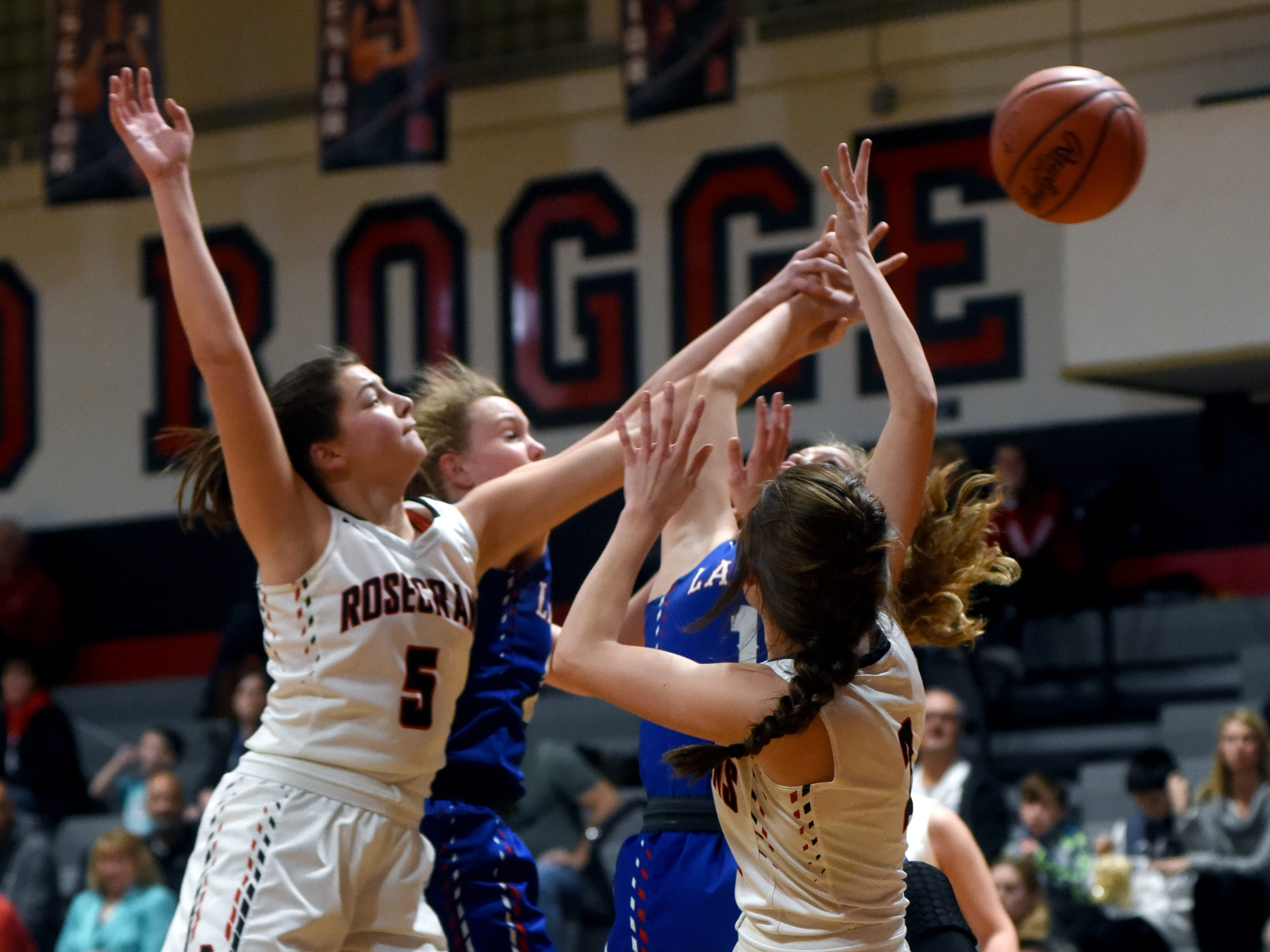 Rosecrans' Maggie Hutcheson, left, fights for a rebound against Lakewood on Monday night at Rogge Gymnasium.