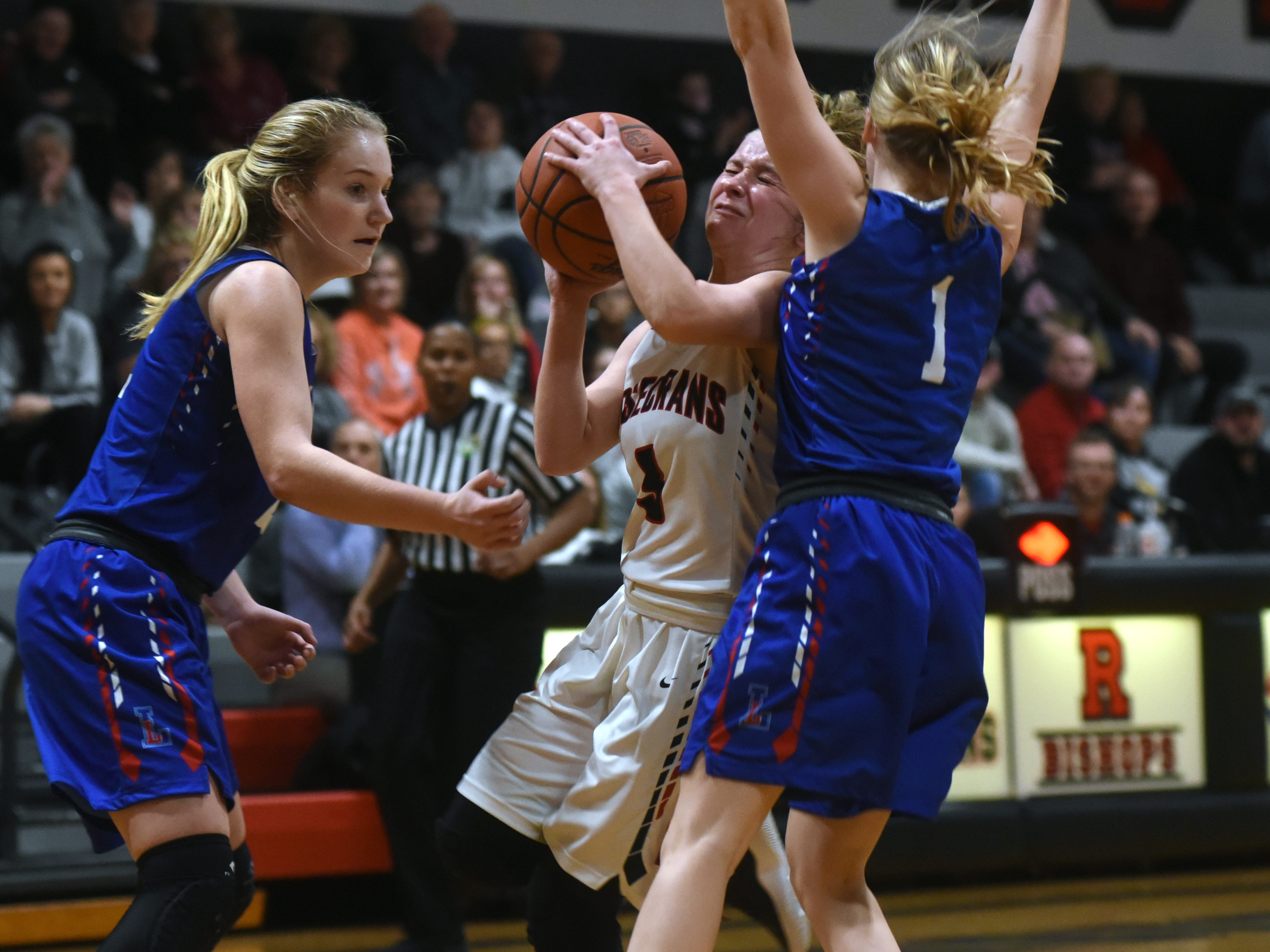 Rosecrans' Claire Creeks drives into traffic against Lakewood on Monday night at Rogge Gymnasium.