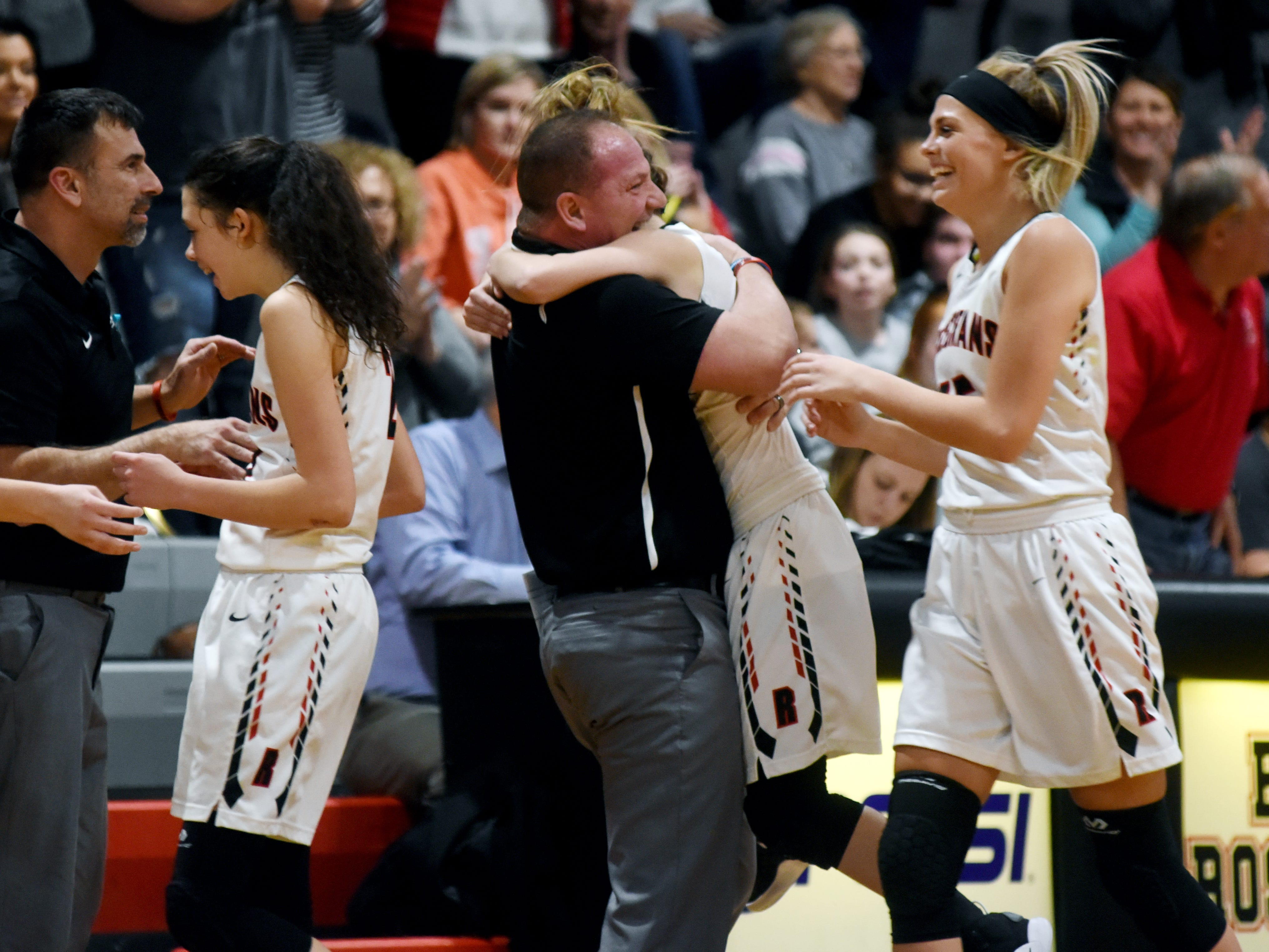 Rosecrans coach Vince Tolson gets a hug from Claire Creeks following the Bishops' 47-44 win against visiting Lakewood on Monday night at Rogge Gymnasium. Creeks scored a team-high 12 points and headed a defense that forced 26 turnovers.