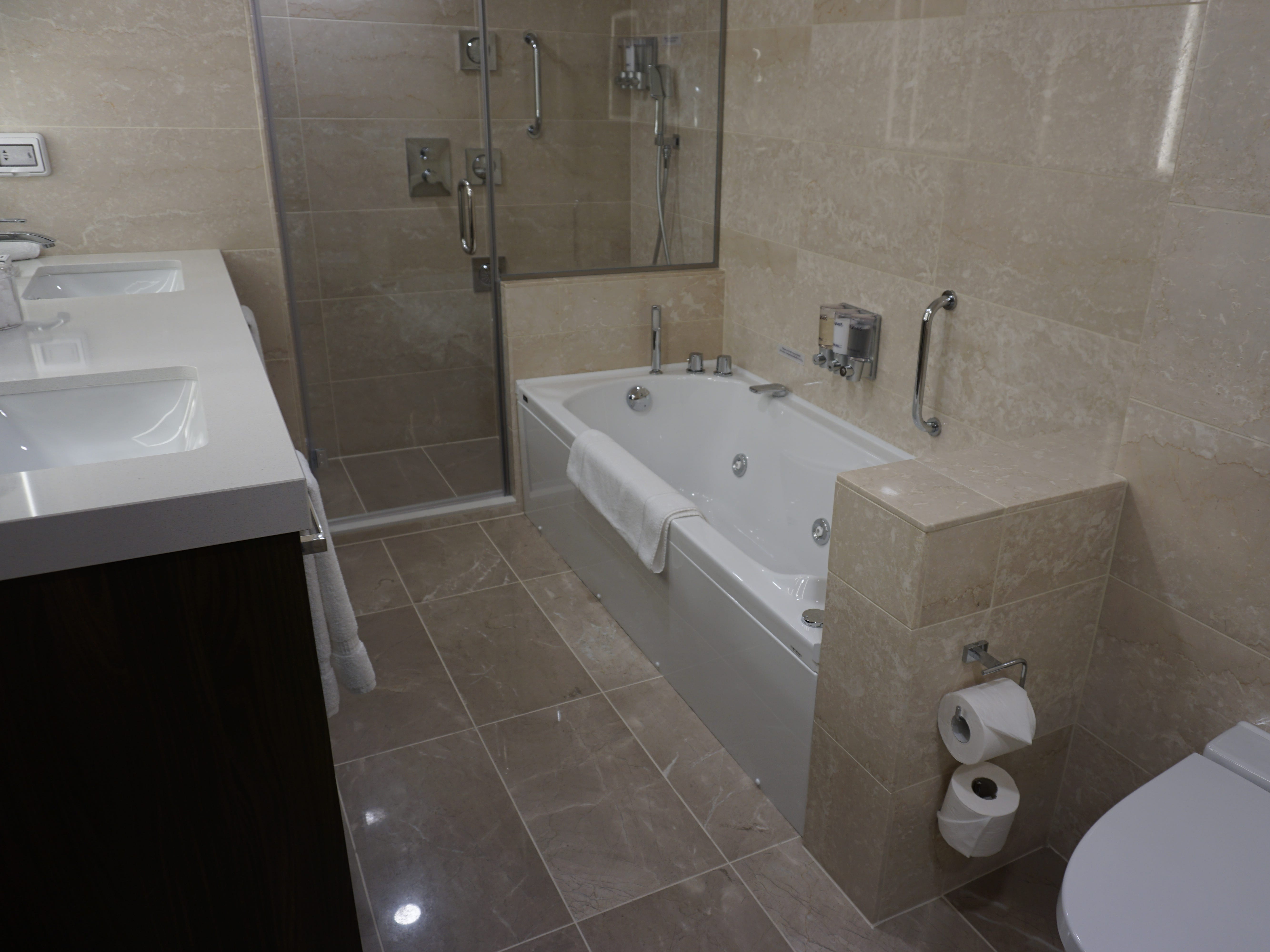Neptune Suite bathrooms are lined in marble and feature a large Jacuzzi tub, a separate shower compartment and twin sinks.