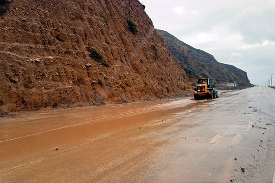 A skip loader clears a river of mud that flowed onto the Pacific Coast Highway in Malibu, Calif.