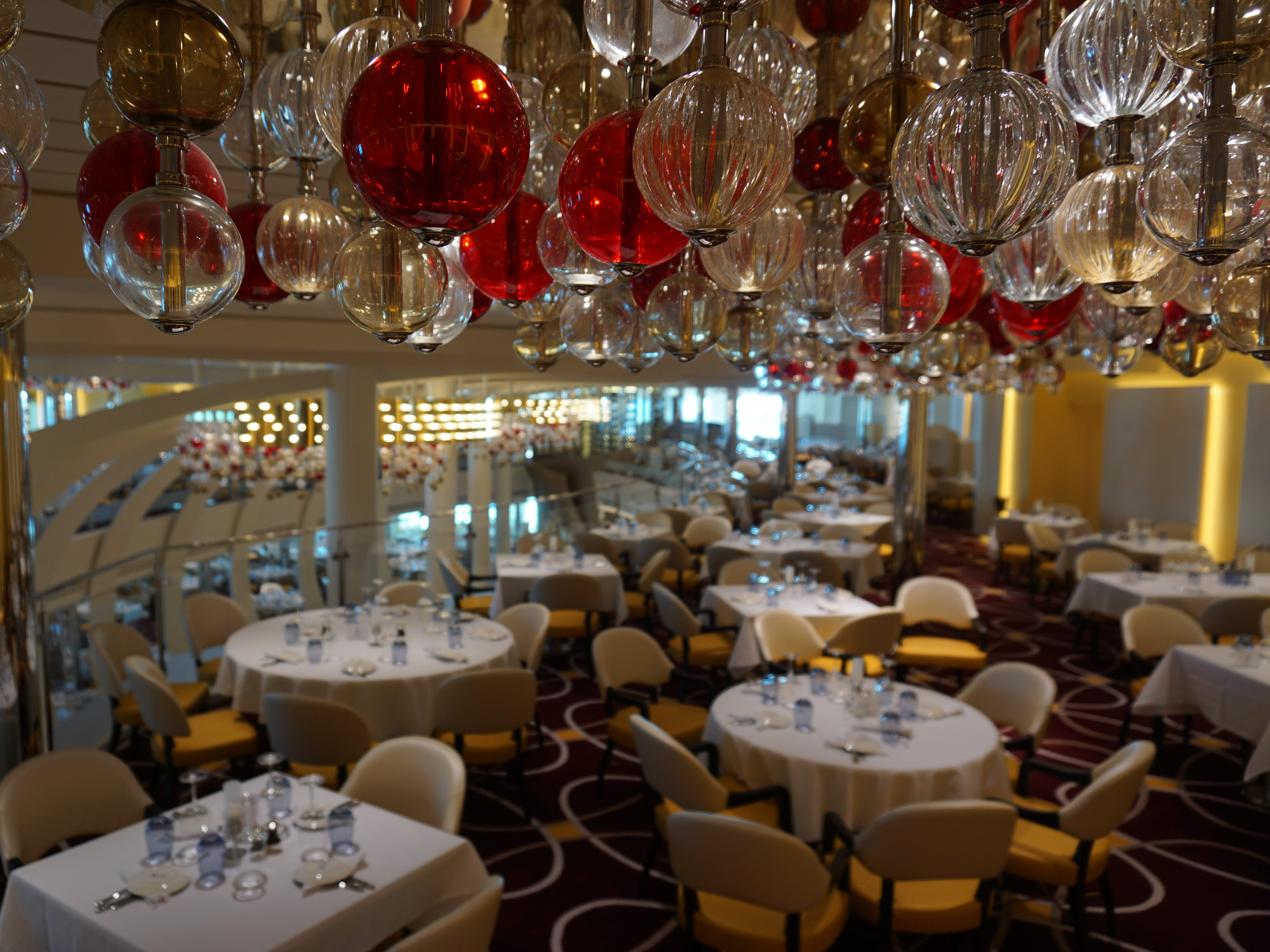 Designed by Adam Tihany, the Dining Room is a double-deck space at the far aft end of Decks 3 and 2.  Hand-blown red, white and gold orbs dangle from its ceiling.