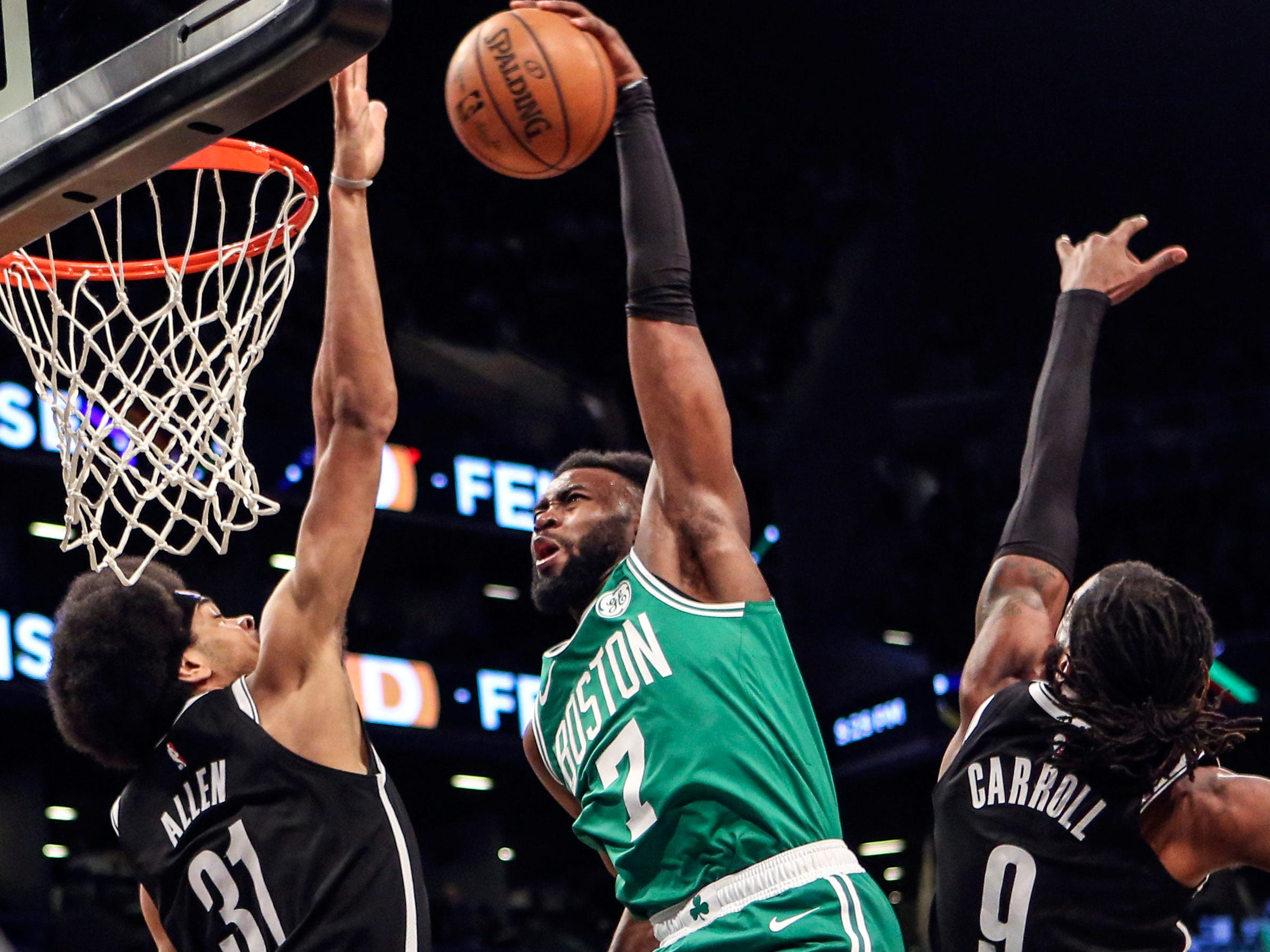 Jan. 14: Celtics forward Jaylen Brown (7) throws down a thunderous one-handed jam between a pair of Nets defenders.