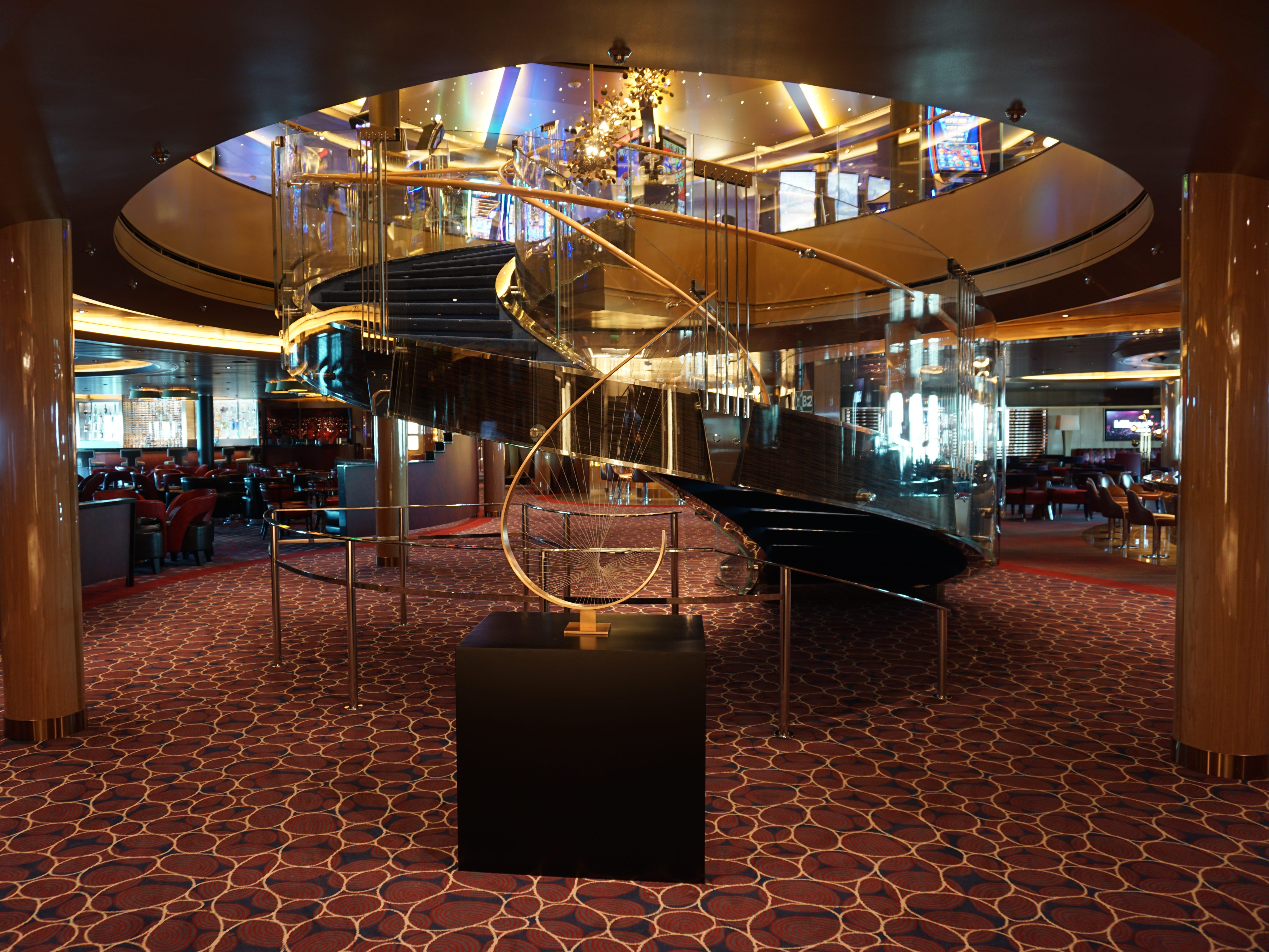 The Music Walk is a multi-faceted entertainment venue on Deck 2. A spiral staircase leading down from the Casino dominates its forward end.