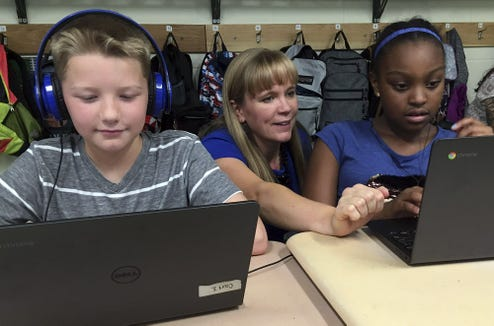 In this Sept. 20, 2018 photo, fifth grade teacher Heather Dalton, center, works with students Julian Ryno, left, and Ma'Kenley Burns, doing math problems on the DreamBox system at Charles Barnum Elementary School in Groton, Conn. A wide array of apps, websites and software used in schools borrow elements from video games to help teachers connect with students living technology-infused lives.