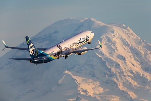 An Alaska Airlines Boeing 737-900 takes off from Seattle-Tacoma International Airport within view of Mount Rainier in November 2018.