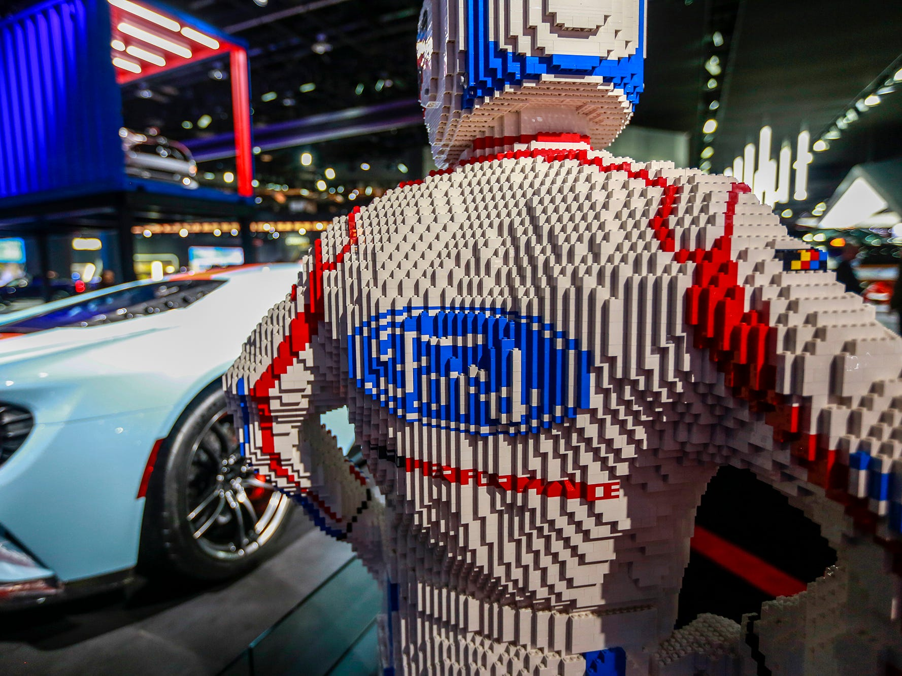 A driver made out of legos looks on at the Ford exhibit.