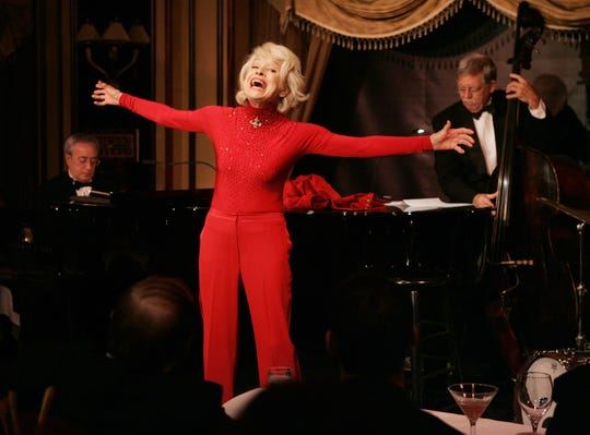 "Broadway legend Carol Channing gives a performance of her one-woman show,""The First 80 Years are the Hardest,"" at the cabaret  Feinstein's at the Regency in New York, Tuesday, Oct. 18, 2005. Channing, 84, was backed up by a trio, including pianist Ken Ascher, left, and Dick Sarpola, right, on bass. (AP Photo/Richard Drew)"