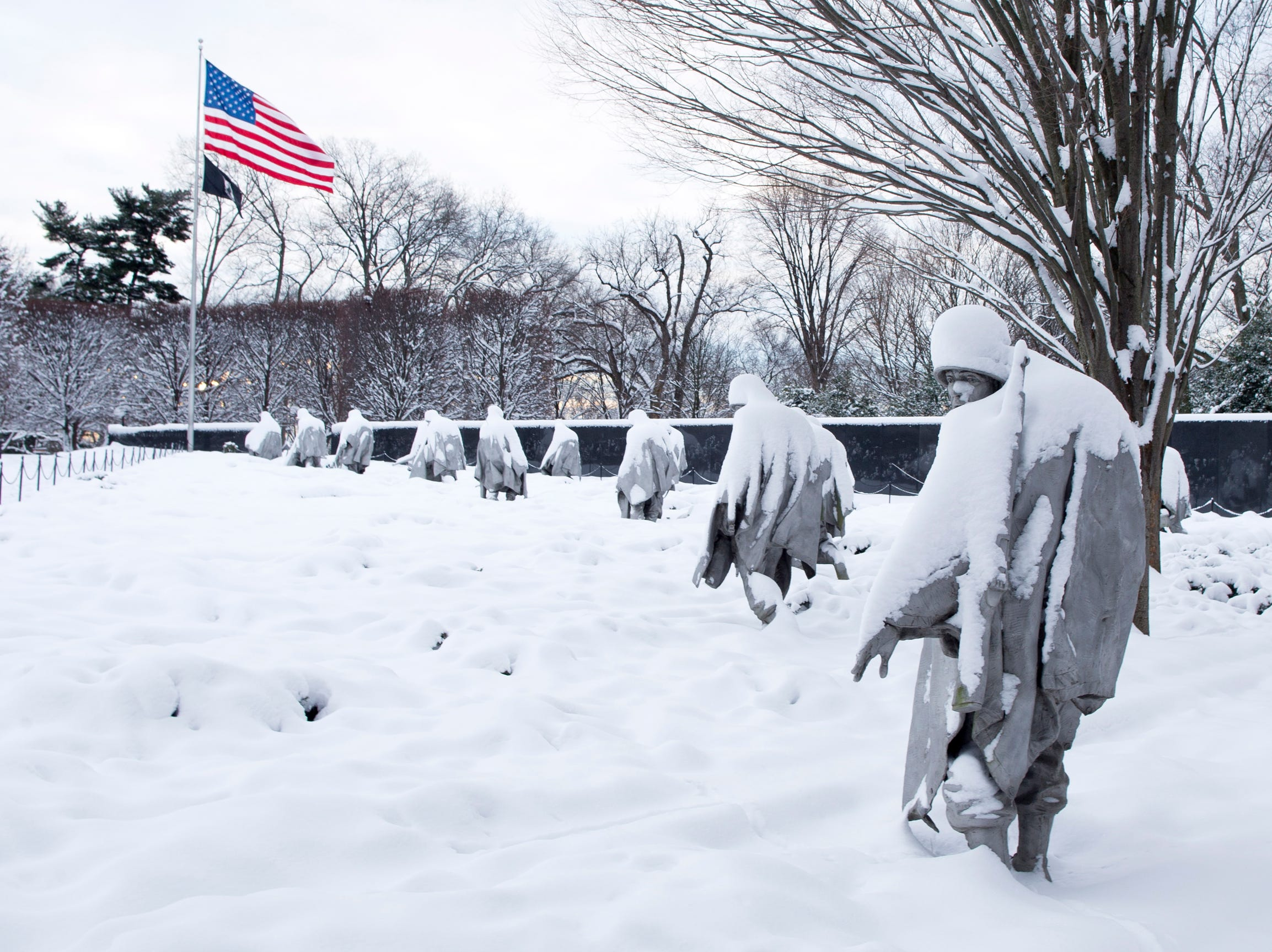 Statues at the Korean War Veterans Memorial are covered in snow in Washington, DC, on Monday.  Federal offices and schools in the nation's capital are closed following a snowstorm this weekend that left an estimated accumulation of 8 to 12 inches of snow in the area. Despite the shutdown of the federal government, the National Park Service announced it would clear snow.  Almost three hundred miles of roads and over one hundred miles of sidewalks in the greater Washington DC area fall under the jurisdiction of the National Park Service.