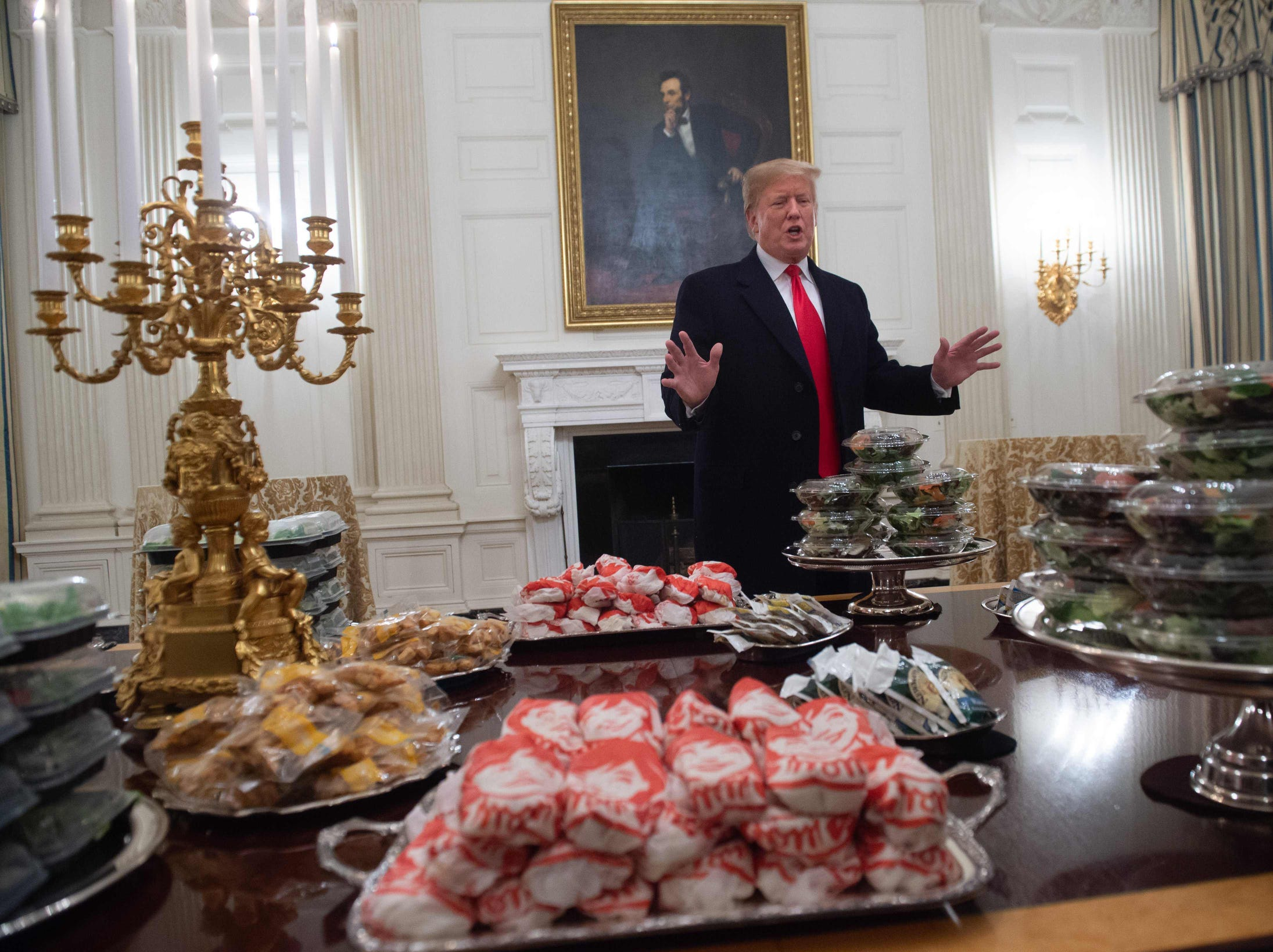 President Donald Trump speaks alongside fast food he purchased for a ceremony honoring the 2018 College Football Playoff National Champion Clemson Tigers in the State Dining Room of the White House in on  Jan. 14, 2019.  Trump says the White House chefs are furloughed due to the partial government shutdown.