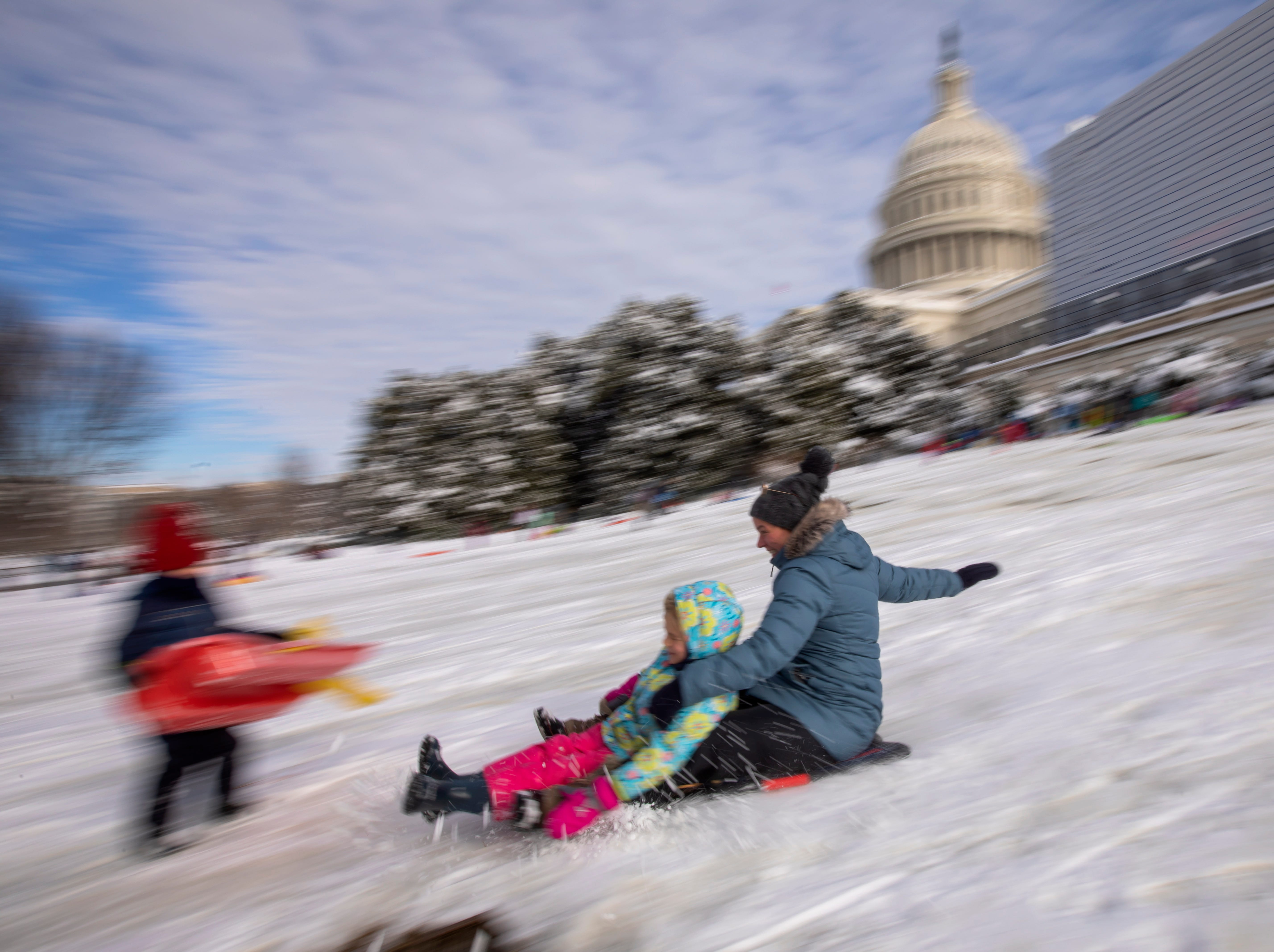epa07283878 Parents and children slide down on the snow at the West Front of the US Capitol after a weekend winter storm in Washington, DC, USA, 14 January 2019. Washington, DC, recorded more than 27 centimeters of snow according to the US National Weather Service. The weather forced the closure of many school systems and most government offices.  EPA-EFE/ERIK S. LESSER