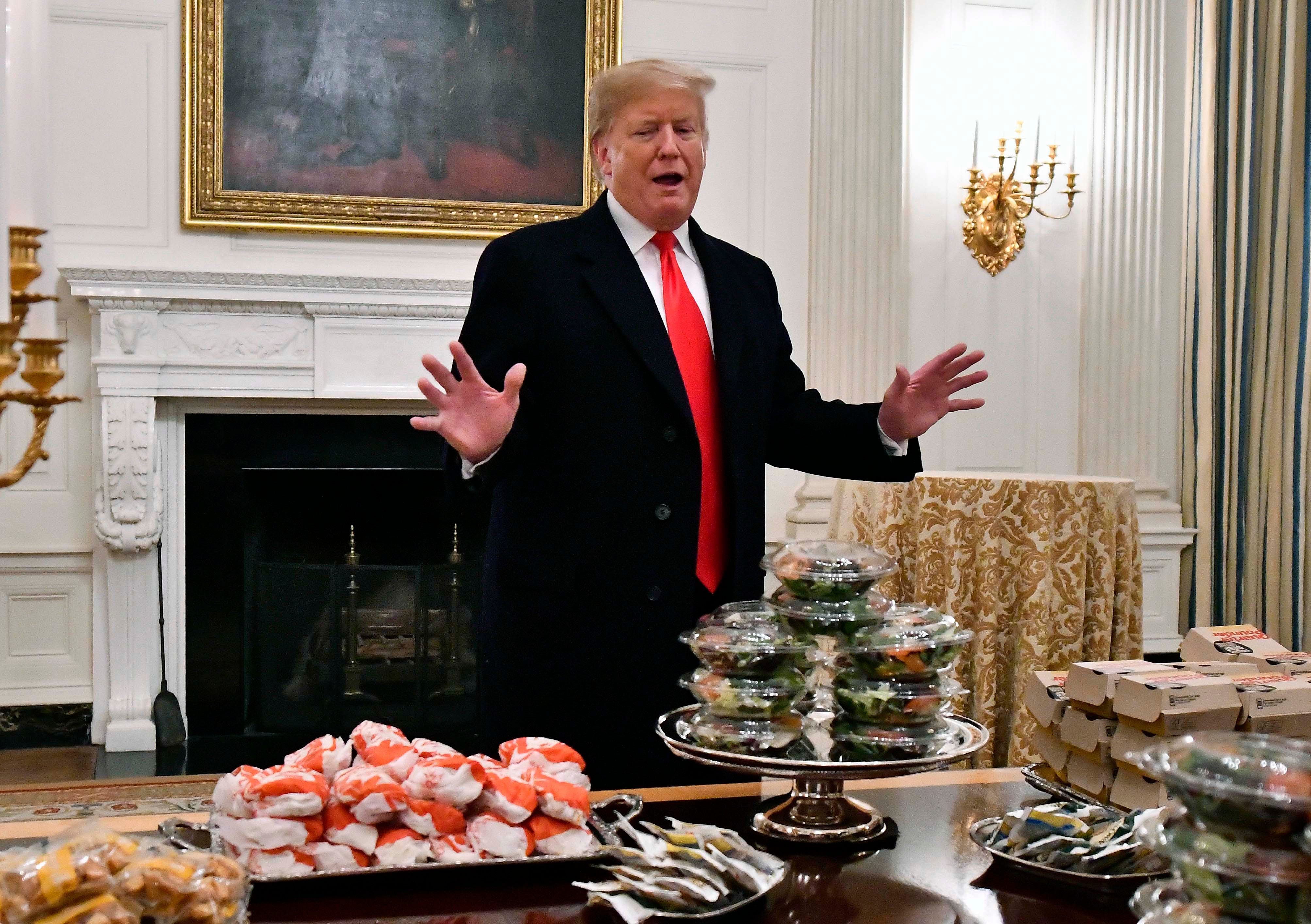 President Donald Trump looks over tables of fast food for the the college football champion Clemson Tigers.