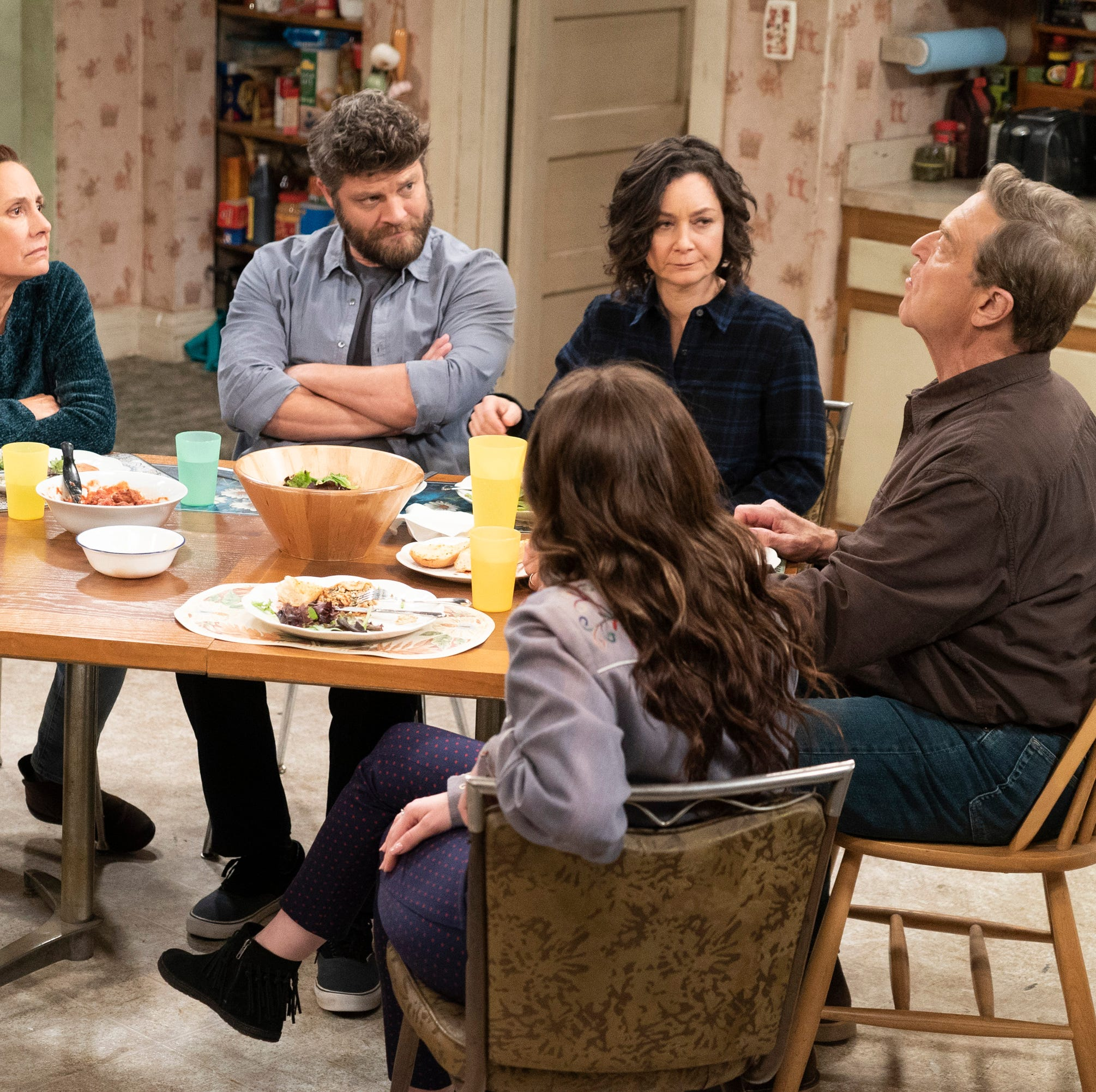 Darlene's beau, Ben (Jay R. Ferguson), third from left, gets the once-over from her family as he joins the Conners for dinner on Tuesday's episode of 'The Conners.'