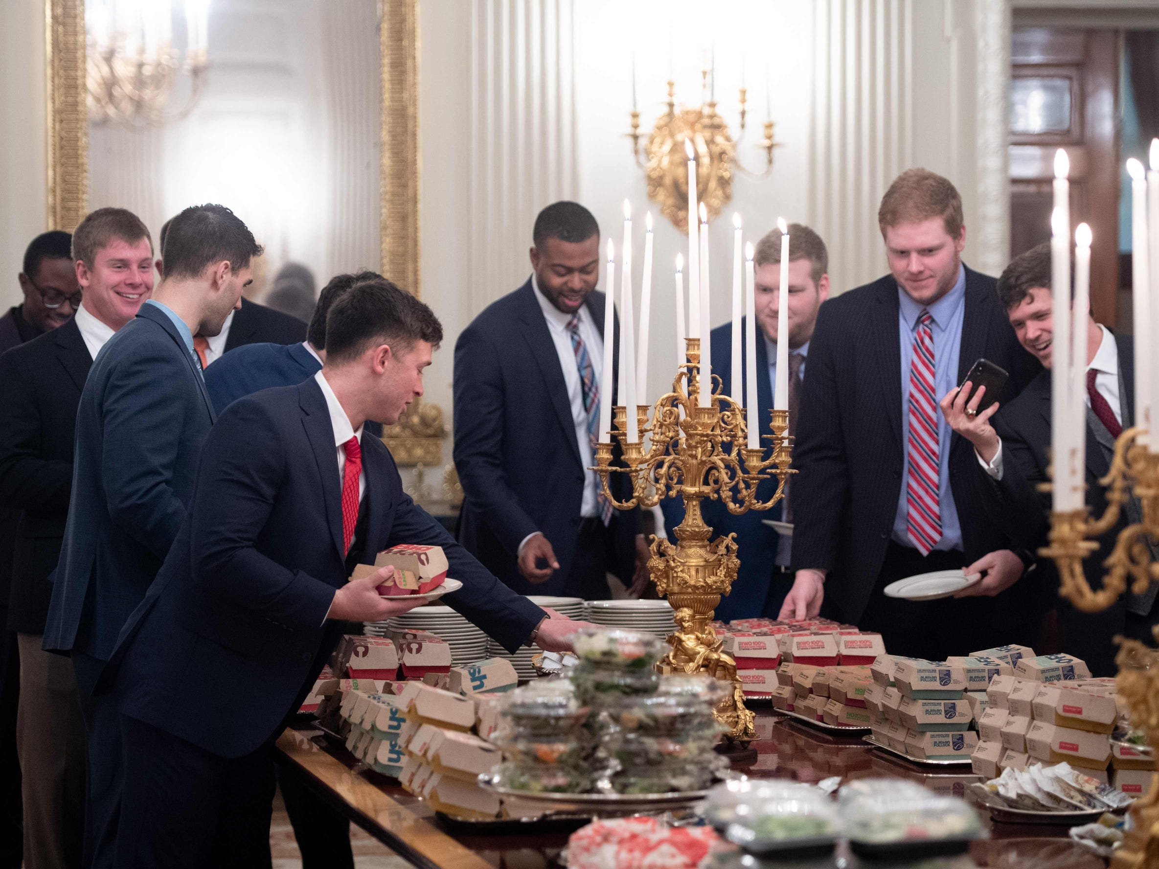 Guests select fast food Donald Trump purchased for a ceremony honoring the 2018 College Football Playoff National Champion Clemson Tigers in the State Dining Room of the White House, Monday.
