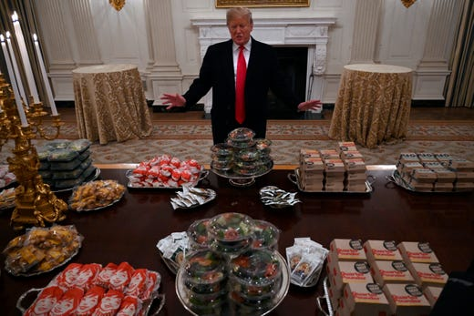President Donald Trump talks to the media about the table full of fast food in the State Dining Room of the White House.