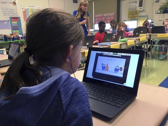 In this Sept. 20, 2018 photo, fifth grade student Ashlynn De Filippis, left, works math problems on the DreamBox system as teacher Heather Dalton, center rear, works with other students in class at Charles Barnum Elementary School in Groton, Conn. A wide array of apps, websites and software used in schools borrow elements from video games to help teachers connect with students living technology-infused lives.