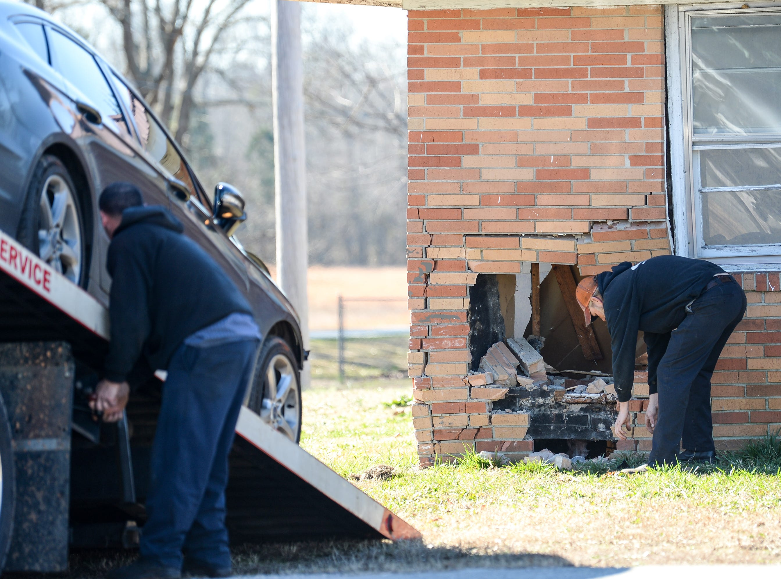 H & H Towing Service of Pelzer picks up pieces after a black Ford Fusion crashed into the brick of the home on 1700 Anderson Parkway at Vernon Street in Williamston Wednesday. Firemen at the scene said the man driving appeared to drive through the American Legion Post 121 parking lot before stopping a three-foot square on the corner of the house before being taken to Greenville for medical care.