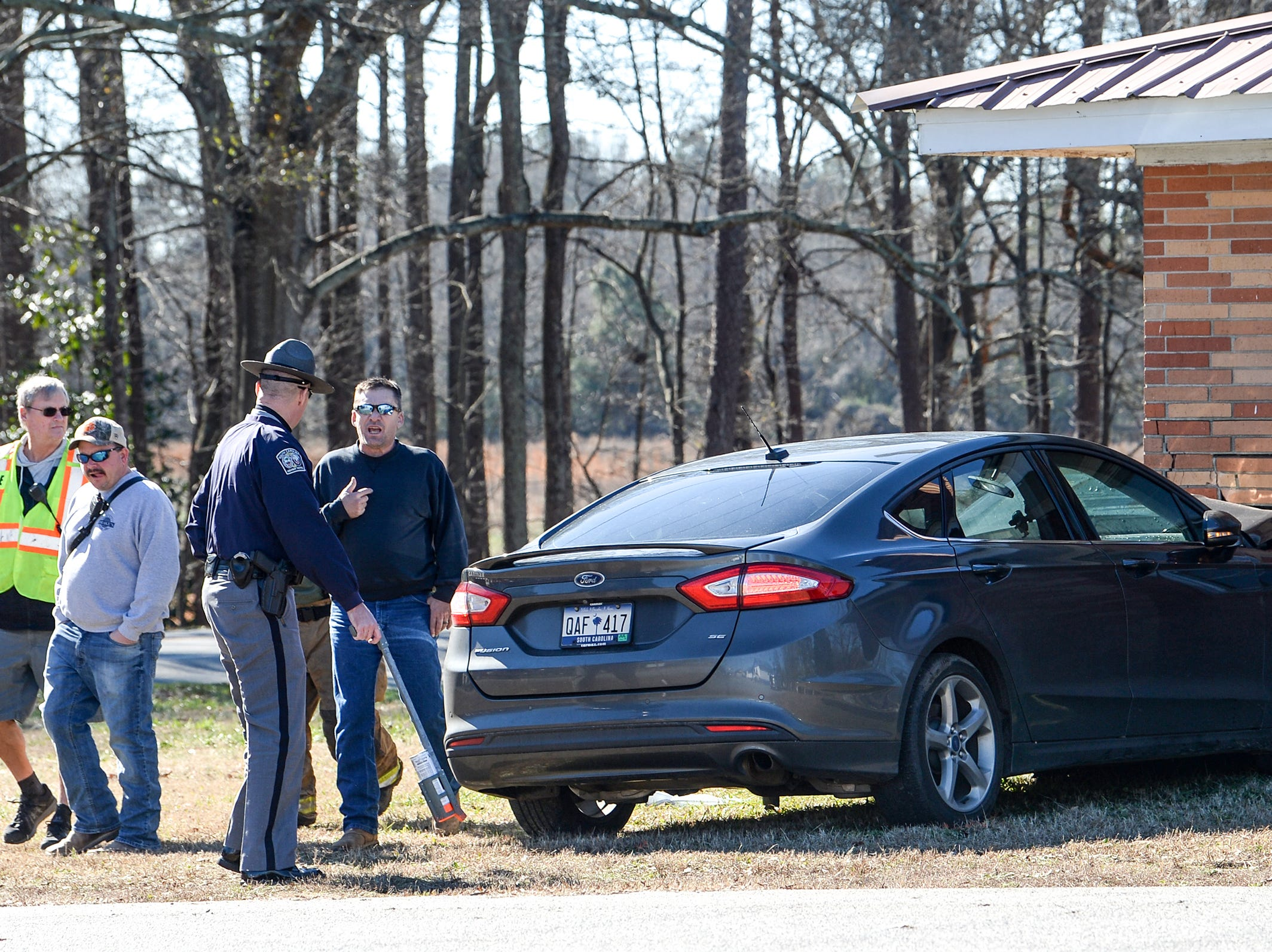 Whitefield station 22 firemen and State Troopers look at a black Ford Fusion up against the home on 1700 Anderson Parkway at Vernon Street in Williamston Wednesday. Firemen said the man driving appeared to drive through the American Legion Post 121 parking lot before stopping a three-foot square on the corner of the house before being taken to Greenville for medical care.