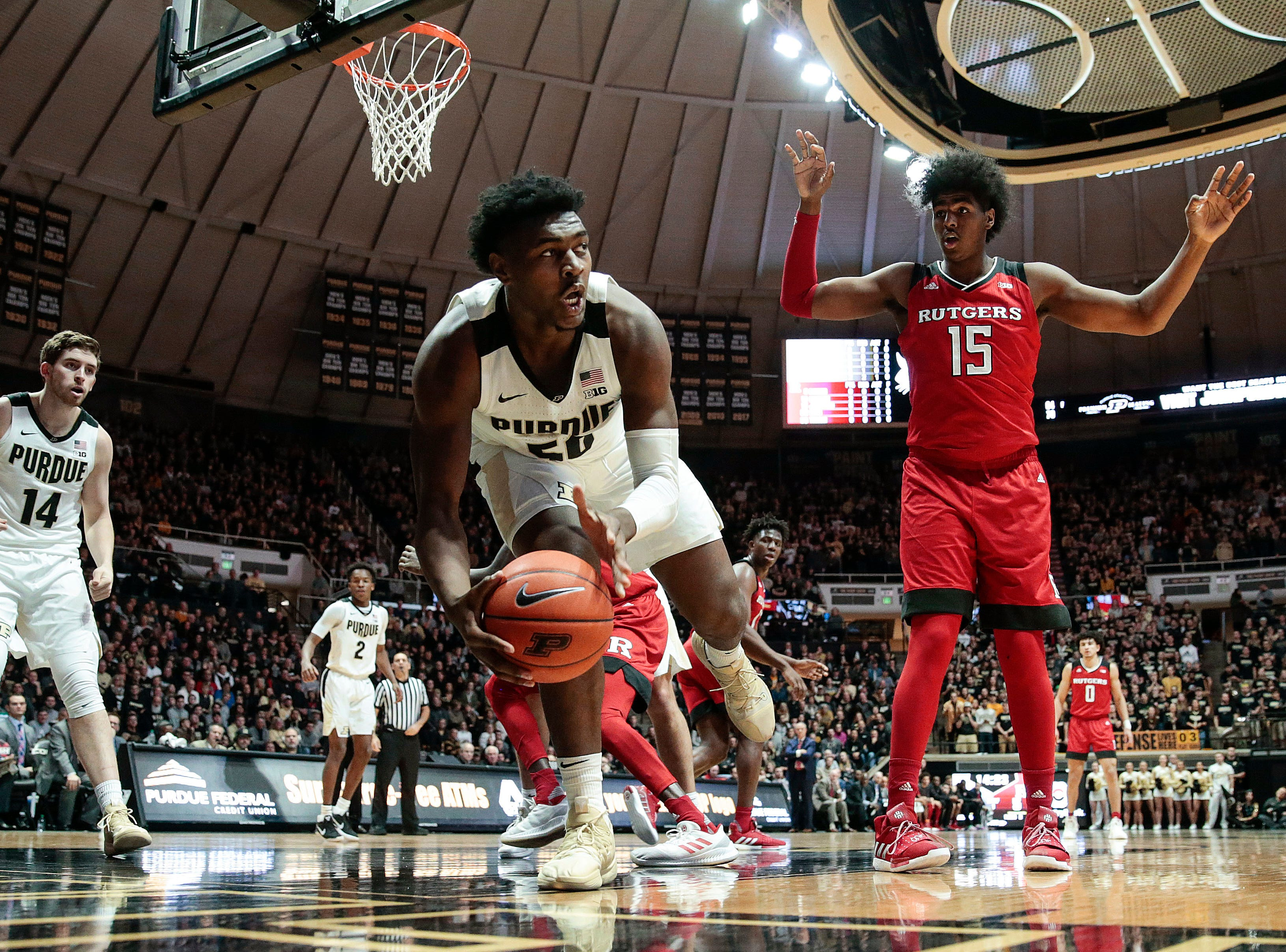 Purdue forward Trevion Williams (50) saves a rebound from going out of bounds in front of Rutgers center Myles Johnson (15)