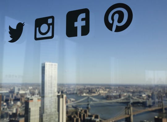 In this 2016, file photo, Icons for Twitter, Instagram, Facebook and Pinterest are displayed on a window in New York. Nearly half of U.S. households carry credit card debt, which means many of the friends making you jealous on Instagram may not be able to afford the vacations they post about.
