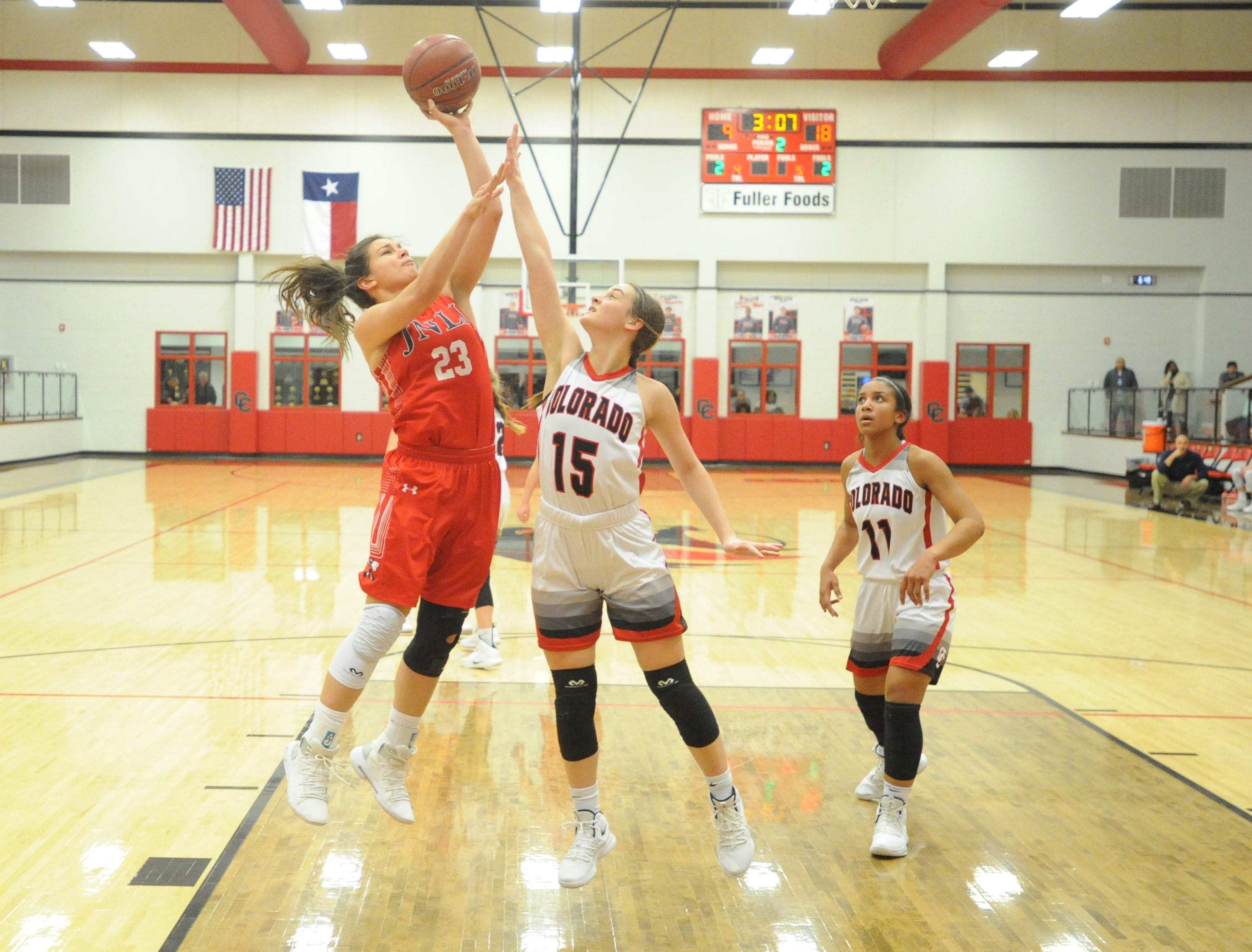 Jim Ned's Libby Tutt (23) goes for a shot in the lane in front of Colorado City guard Kaci Hudson (15).