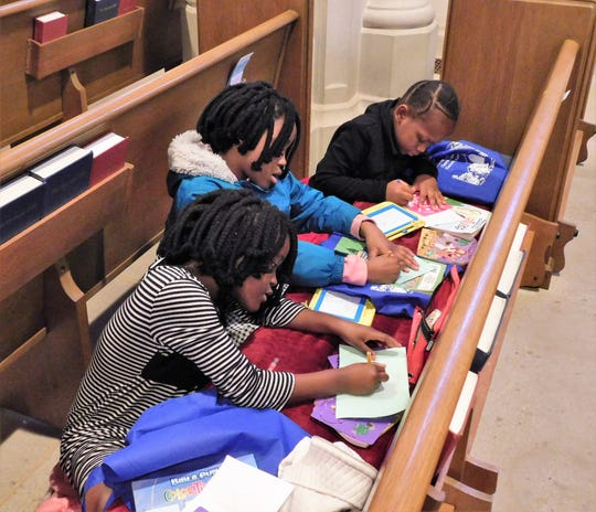 Children enjoy coloring during a Swahili language service at Episcopal Church of the Heavenly Rest.