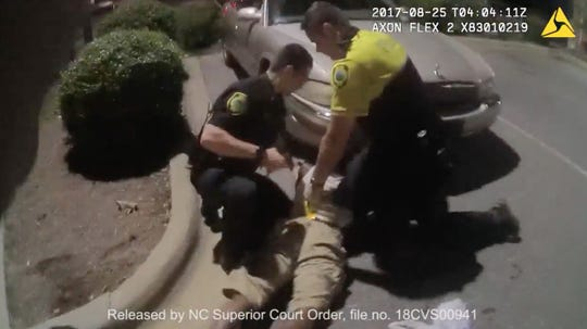 In body camera footage from Asheville police officer Luis Delgado shows a struggle between then-officer Christopher Hickman, Officer Verino Ruggiero and Johnnie Rush during an altercation following his stop for jaywalking on August 25, 2017.