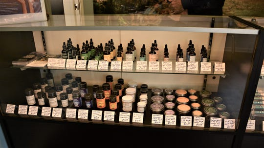 An assortment of CBD tinctures lined up in the display case at High Country Vapor and CBD.