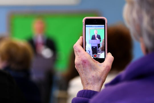 An attendee makes a video of the press conference Wednesday in Asheville at which North Carolina Attorney General Josh Stein announced that he does not object to HCA Healthcare's purchase of Mission Health.