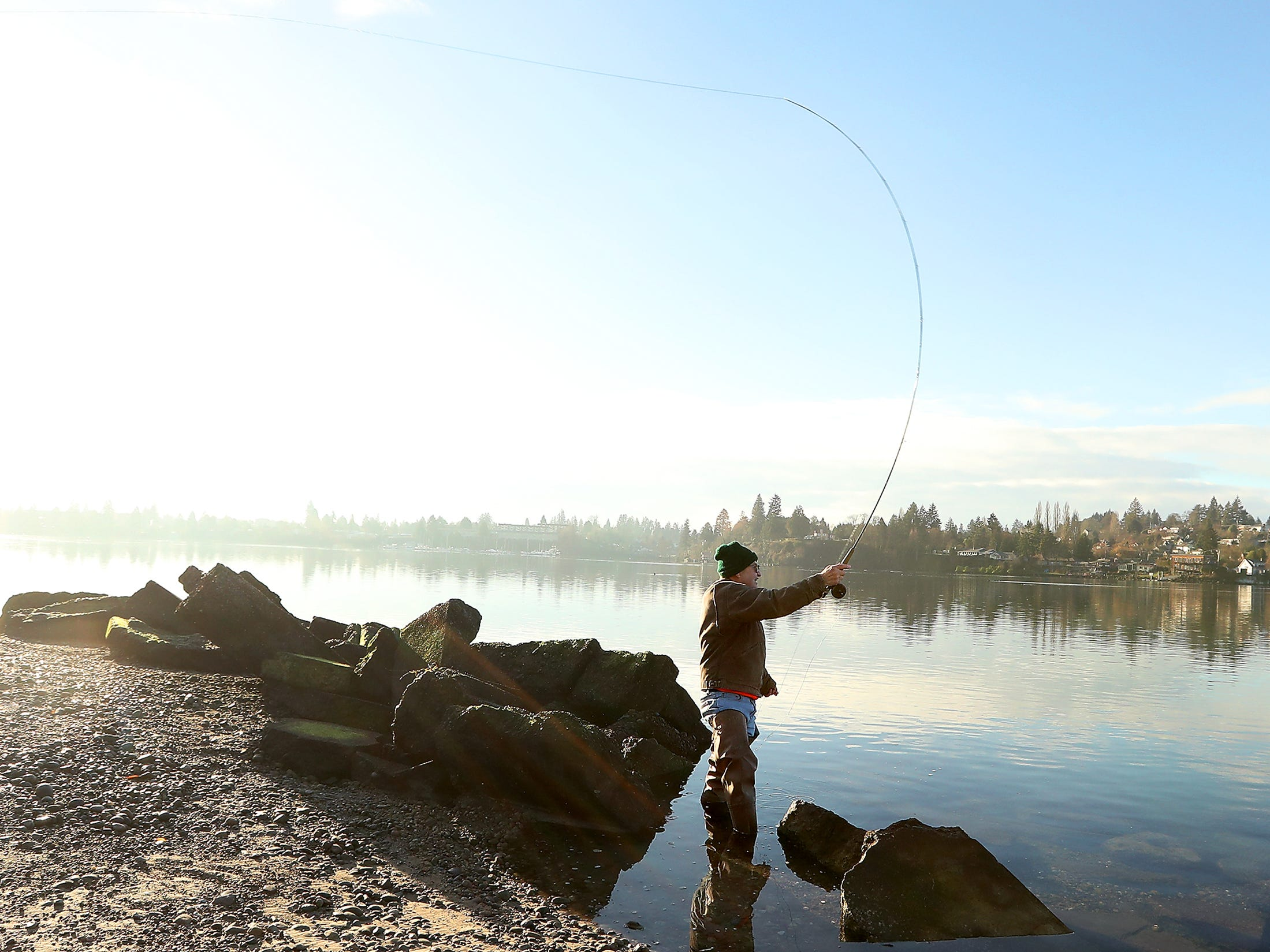 Kitsap Poggie Club member Henry Altenburg takes advantage of the crisp sunny morning to cast his line out in search for sea-run cutthroat trout at Pat Carey Vista in Bremerton on Wednesday, January 16, 2019.
