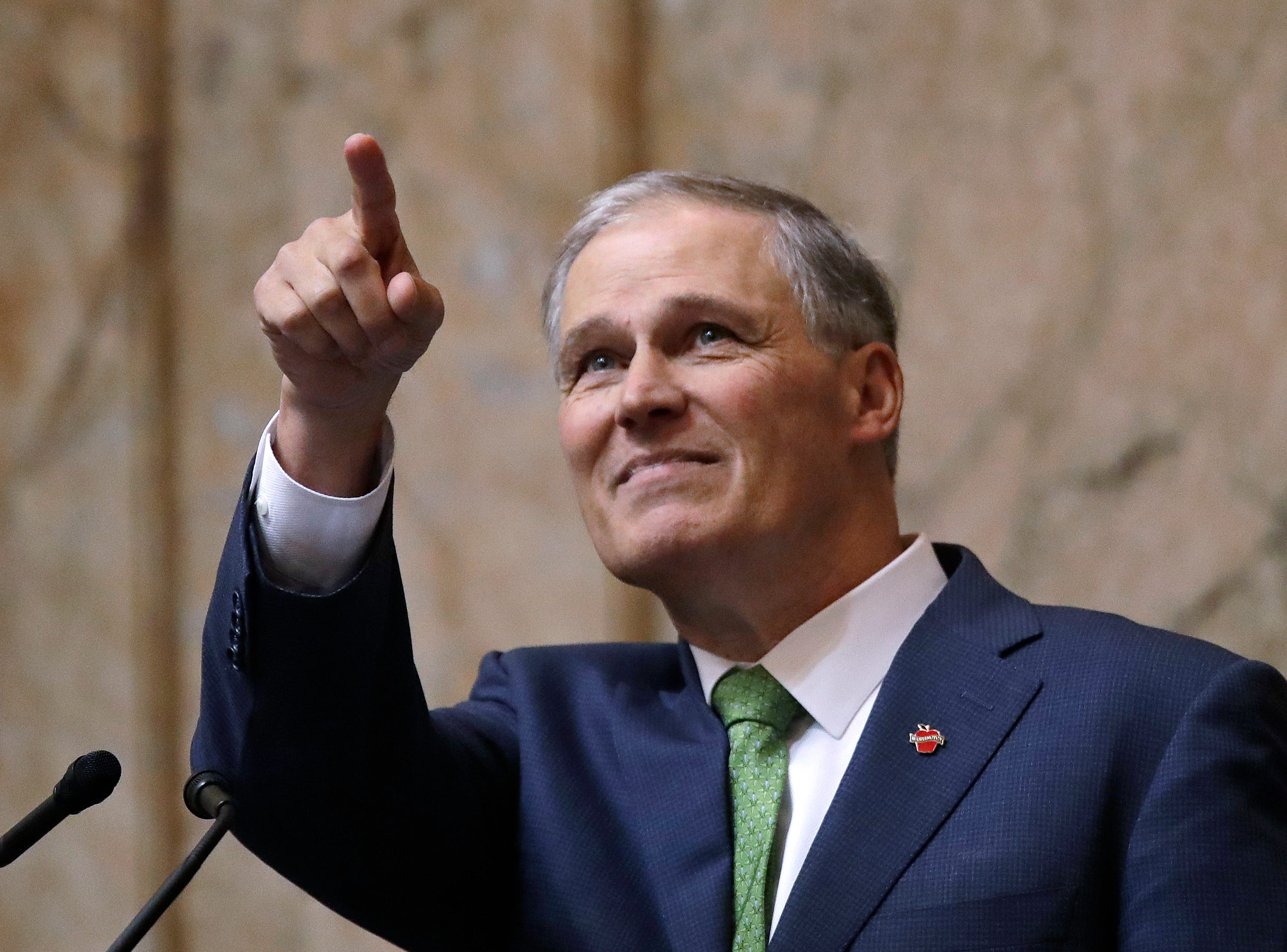 Gov. Jay Inslee points toward the gallery, where his family sat, after concluding his State of the State address Tuesday in Olympia. Inslee, who is mulling a 2020 White House bid, highlighted his clean energy agenda in the annual speech.