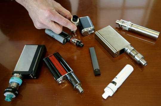 A high school principal displays vaping devices that were confiscated from students in such places as restrooms or hallways at the school in Massachusetts.