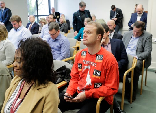 Anti-tax activist Tim Eyman, wearing a shirt adorned with stickers promoting his $30 car tabs initiative, attended the Associated Press Legislative Preview on Jan. 10 in Olympia.