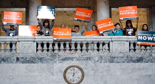 Children hold signs in support of gun safety legislation as they stand on a balcony in the Capital rotunda before Gov. Jay Inslee's State of the State address.