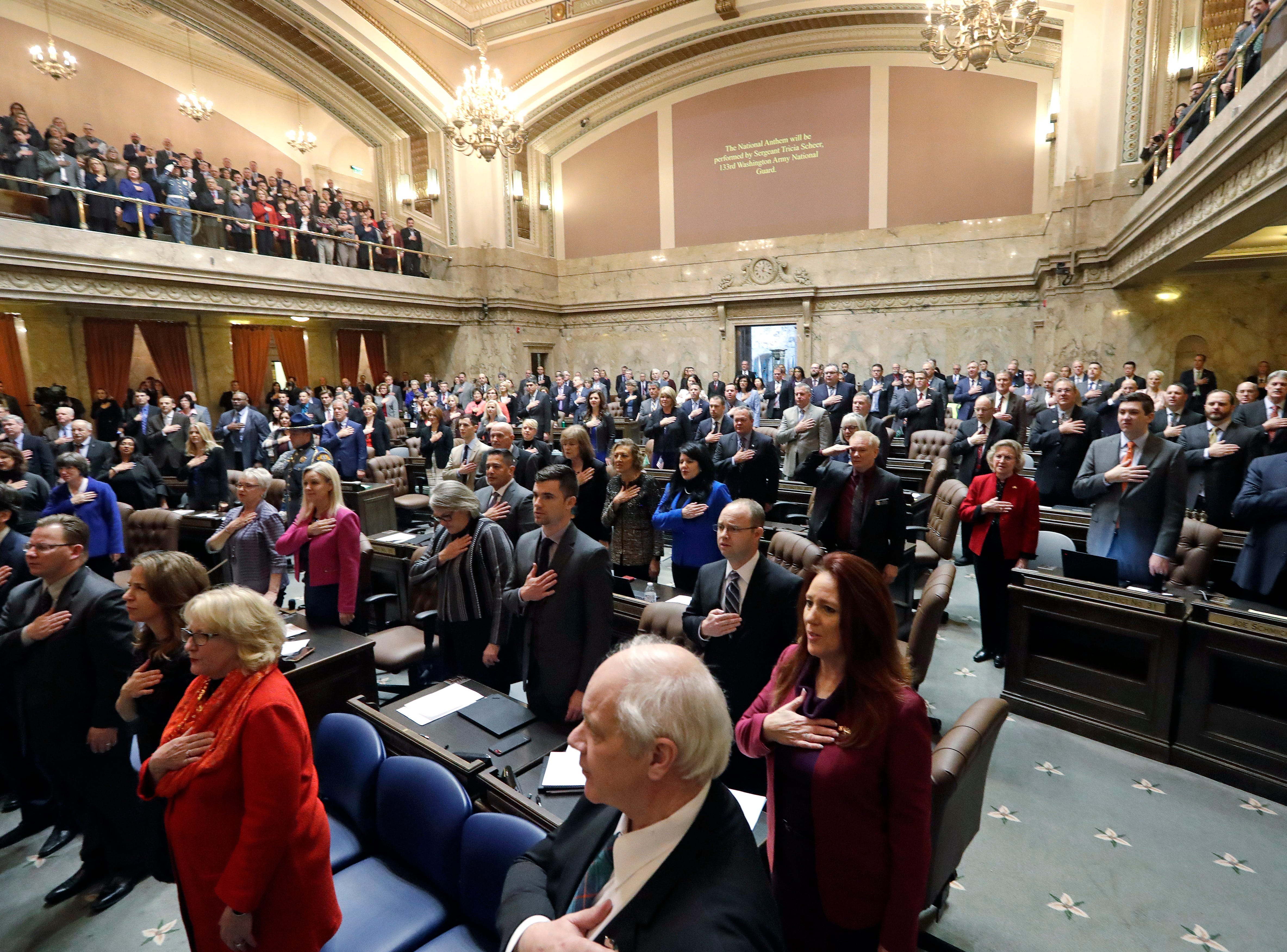 Legislators and guests stand for the national anthem before Gov. Jay Inslee's state of the state speech Tuesday in Olympia.