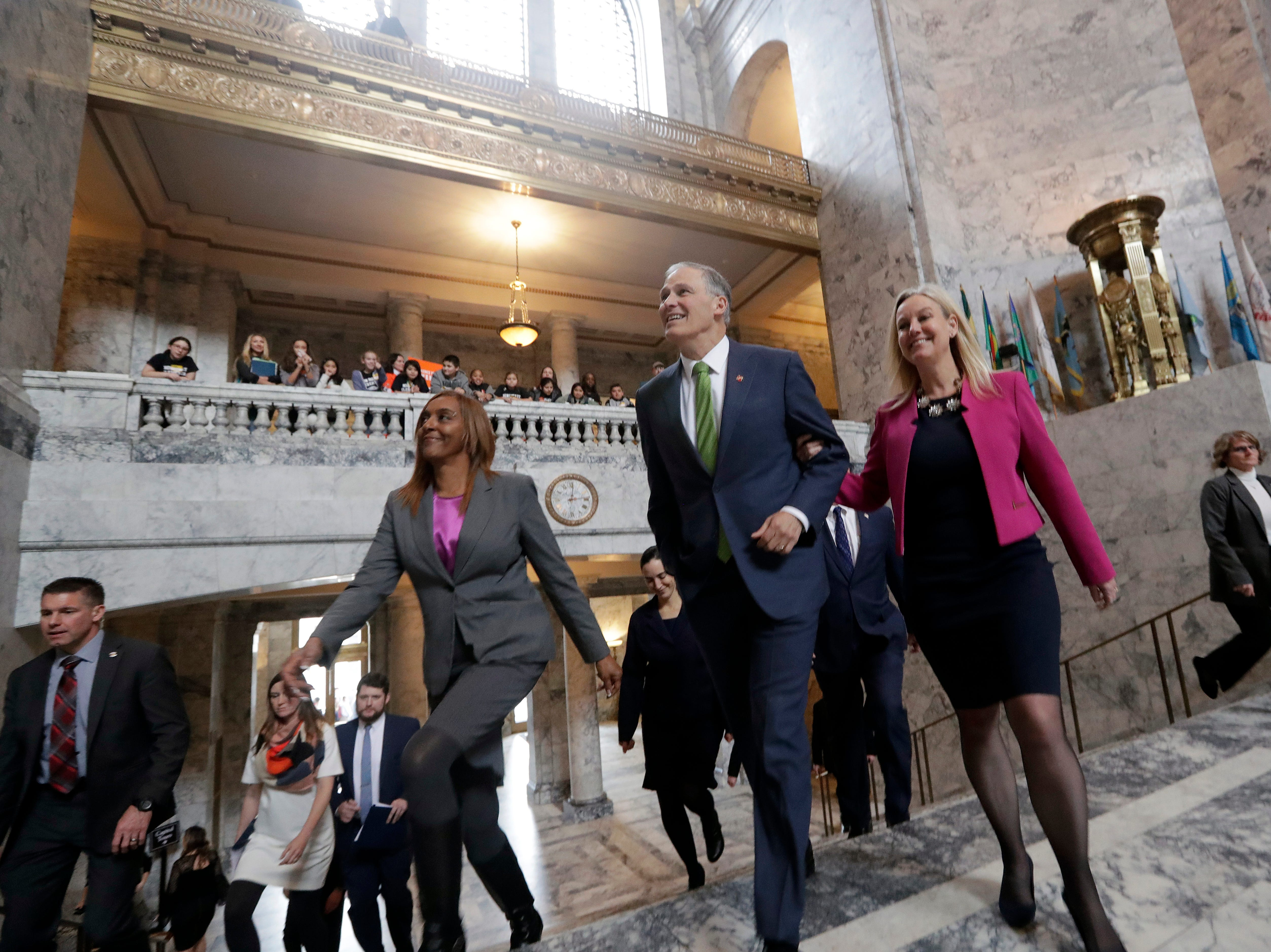 Gov. Jay Inslee is escorted through the Capital rotunda and to the House chambers by Rep. Mary Dye, right, R-Pomeroy, and Rep. Melanie Morgan, D-Lakewood, before his State of the State address Tuesday in Olympia.