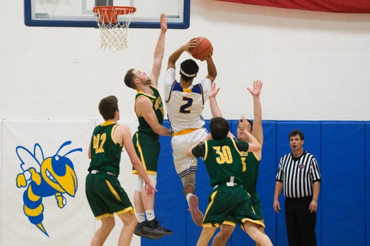 "Milton's Colin Mathis (2) leaps for a lay up over BFA""S Kameron Dunsmore (14) during the boys basketball game between the BFA St. Albans Bobwhites and the Milton Yellowjackets at Milton High School on Tuesday night January 15, 2019 in Milton."