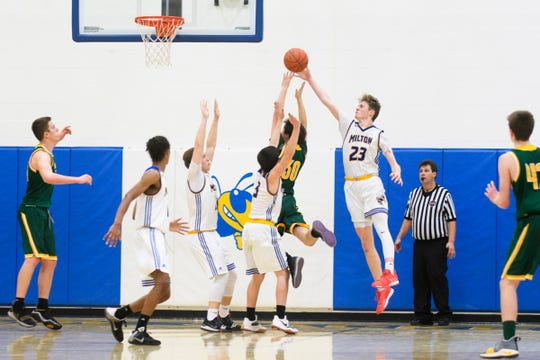 Milton's Ian Jennings (23) leaps to block the shot by BFA's Ben Archambault (30) during the boys basketball game between the BFA St. Albans Bobwhites and the Milton Yellowjackets at Milton High School on Tuesday night January 15, 2019 in Milton.