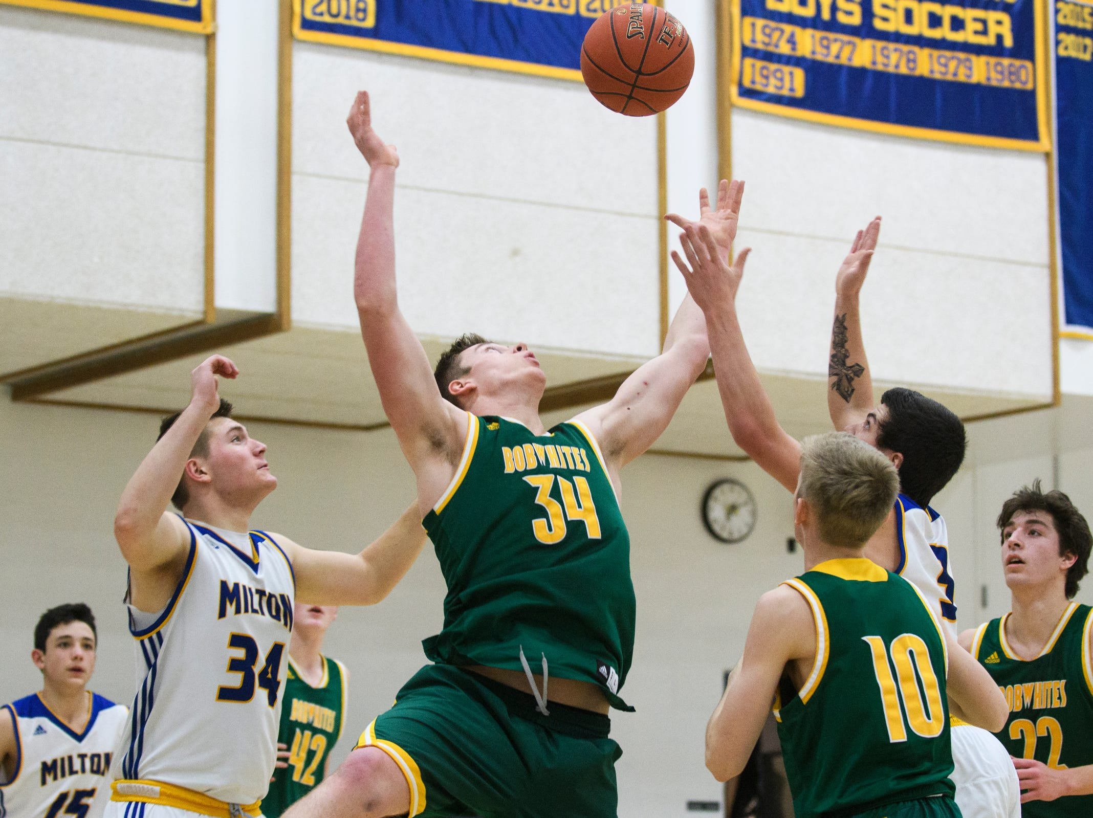 BFA's Nick Voyer (34) battles for the rebound with Milton's Coby Mason (34) and Colby Ducharme (3) during the boys basketball game between the BFA St. Albans Bobwhites and the Milton Yellowjackets at Milton High School on Tuesday night January 15, 2019 in Milton.