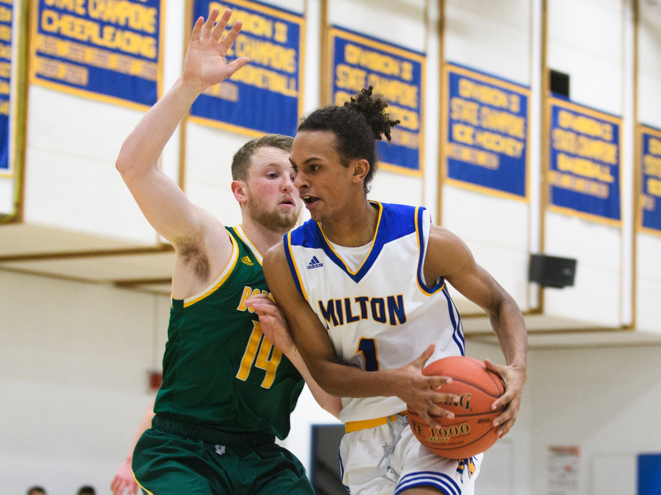 Milton's Sam Patterson (1) drives to the hoop past BFA's Kameron Dunsmore (14) during the boys basketball game between the BFA St. Albans Bobwhites and the Milton Yellowjackets at Milton High School on Tuesday night January 15, 2019 in Milton.