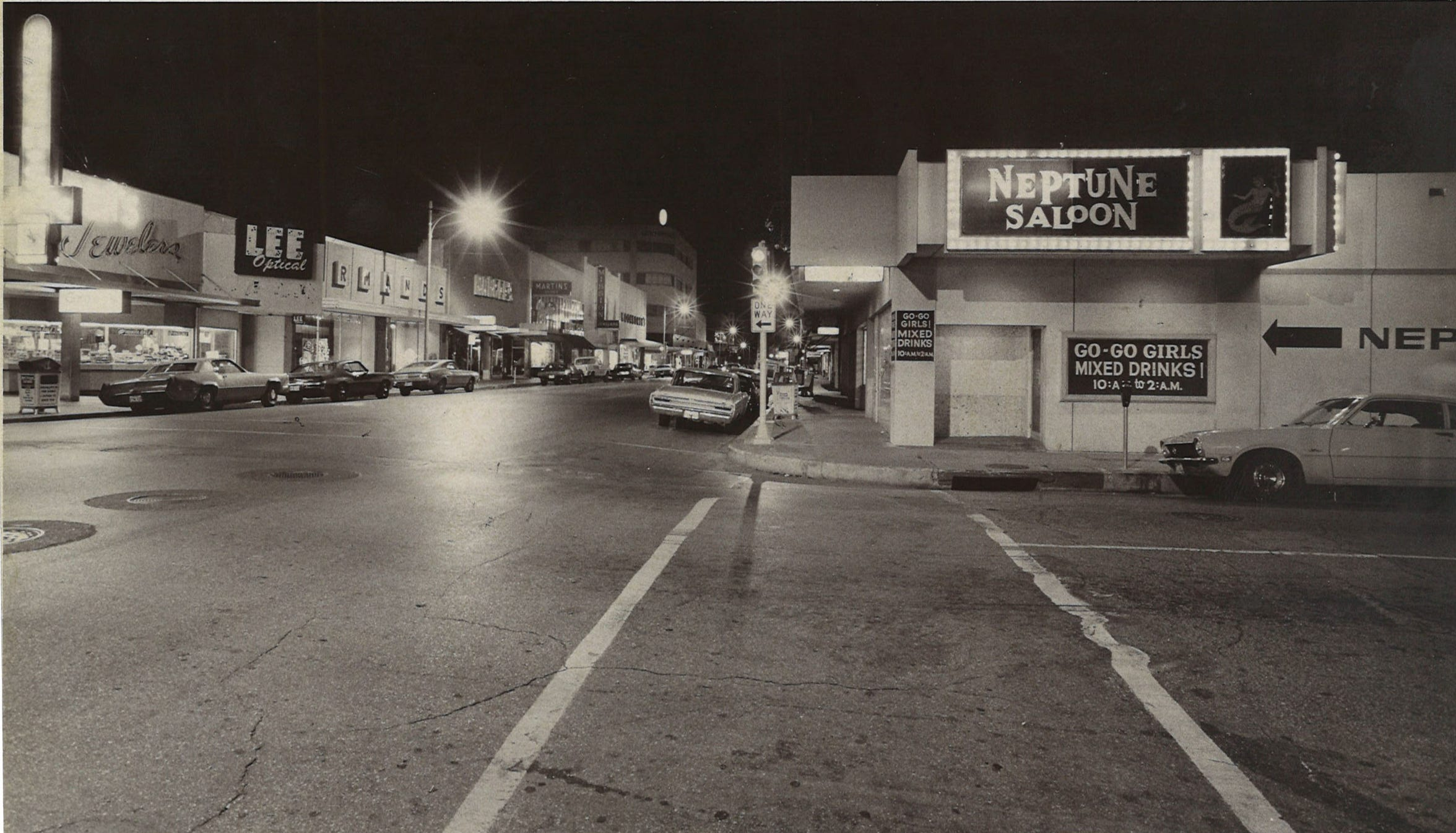 The intersection of Chaparral and William street in June 1975 in downtown Corpus Christi. Neptune Saloon, Green's Jewelers and Lee Optical are among the store visible in the shot.