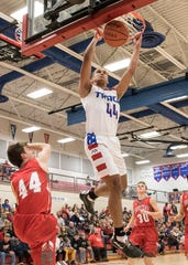 Junior Triton Davidson hangs off the rim after dunking the ball to score for Zane Trace during the first quarter of their game against Johnstown Monroe Tuesday night at Zane Trace High School.
