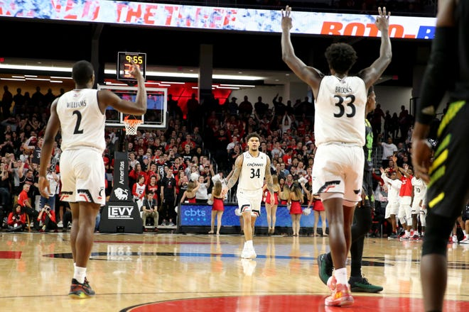 Cincinnati Bearcats guard Jarron Cumberland (34), center, is congratulated on a made 3-point shot by Cincinnati Bearcats guard Keith Williams (2), left, and Cincinnati Bearcats center Nysier Brooks (33) in the first half of an NCAA college basketball game against the South Florida Bulls, Tuesday, Jan. 15, 2019, at Fifth Third Arena in Cincinnati.