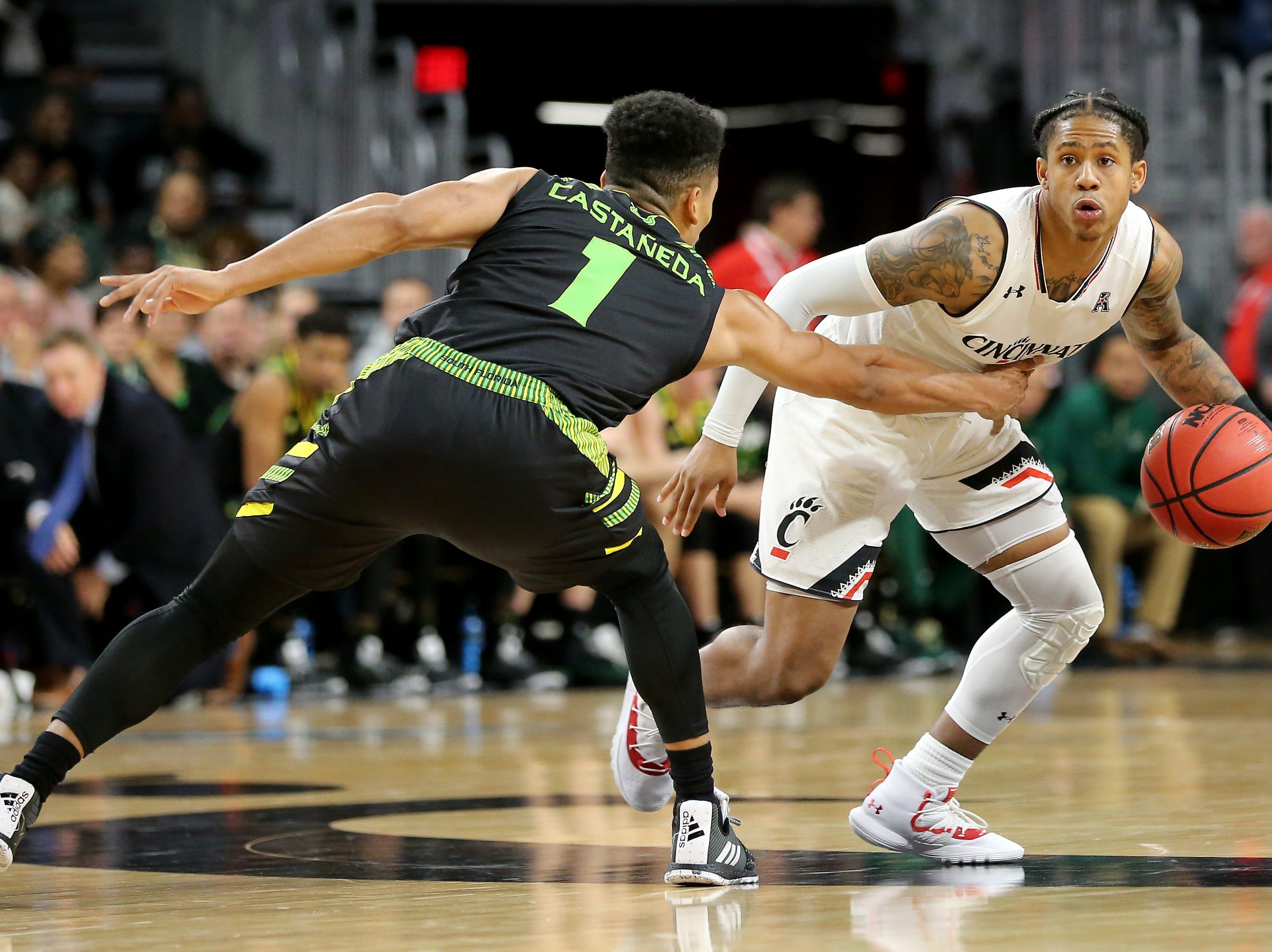 Cincinnati Bearcats guard Justin Jenifer (3) brings the ball up court as South Florida Bulls guard Xavier Castaneda (1) defends in the second half of an NCAA college basketball game, Tuesday, Jan. 15, 2019, at Fifth Third Arena in Cincinnati. Cincinnati won 82-74.