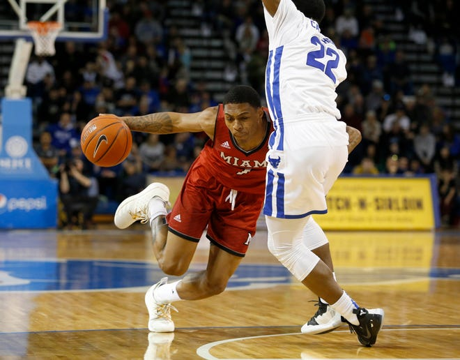 Miami Redhawks guard Nike Sibande (1) drives to the basket as Buffalo Bulls guard Dontay Caruthers (22) tries to defend during the second half at Alumni Arena.