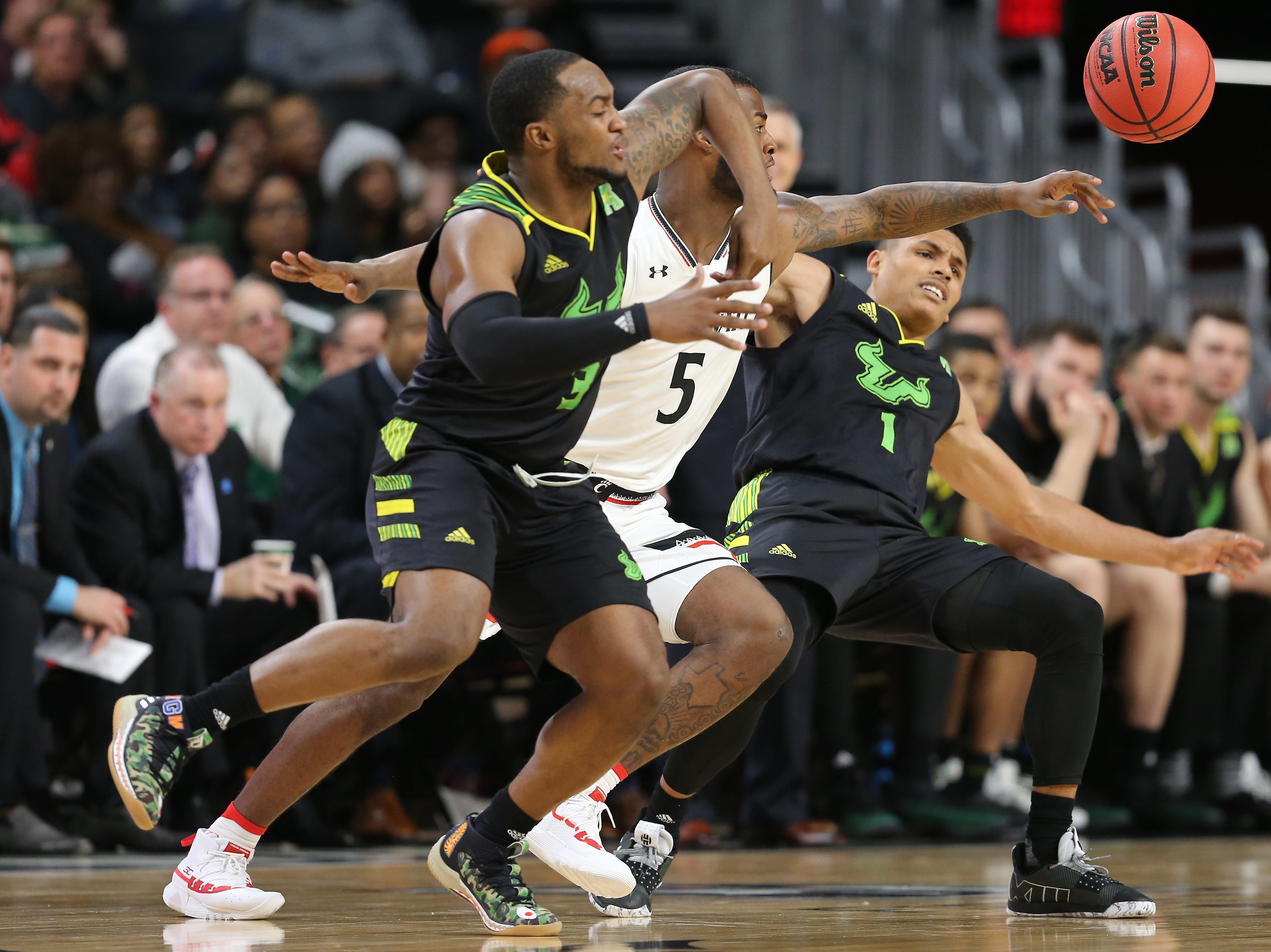 Cincinnati Bearcats guard Trevor Moore (5) is called for a foul after going for the steal of South Florida Bulls guard Xavier Castaneda (1) in the second half of an NCAA college basketball game, Tuesday, Jan. 15, 2019, at Fifth Third Arena in Cincinnati. Cincinnati won 82-74.