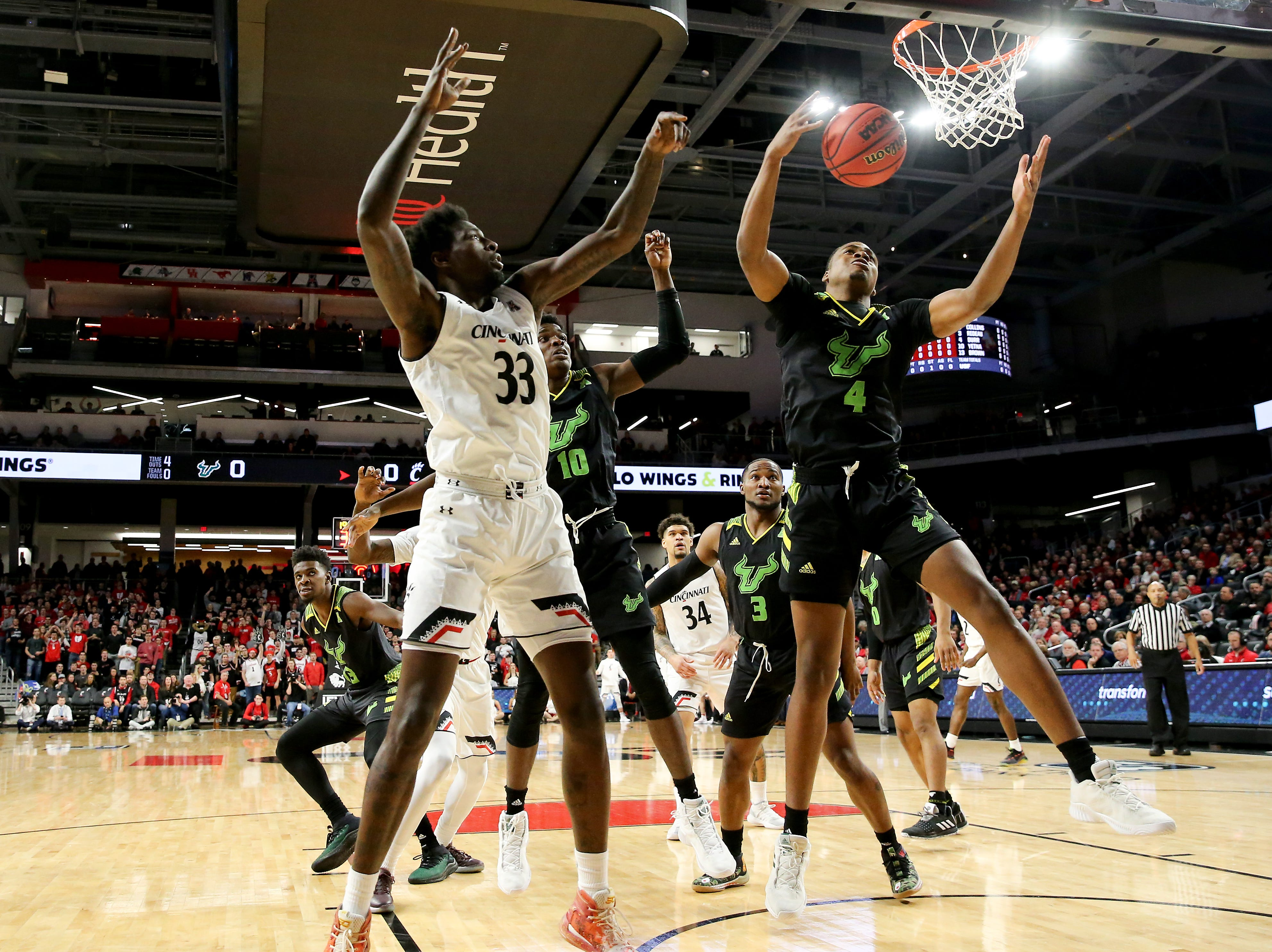 Cincinnati Bearcats center Nysier Brooks (33) and South Florida Bulls forward Michael Durr (4) battle for a rebound in the first half of an NCAA college basketball game, Tuesday, Jan. 15, 2019, at Fifth Third Arena in Cincinnati.