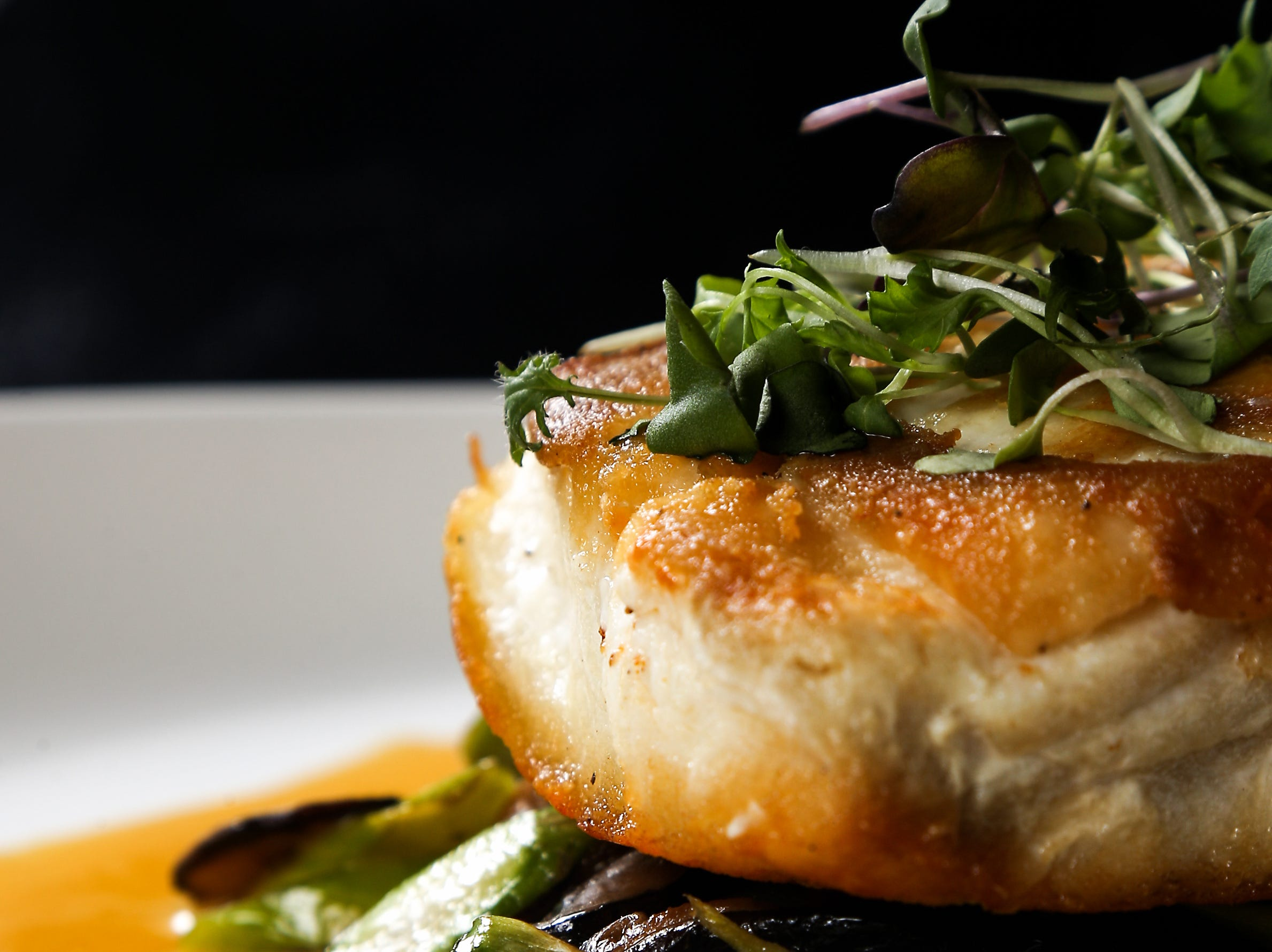The Atlantic halibut, with asparagus mushroom and orange corn reduction, pictured, Tuesday, Jan. 15, 2019,at Galla Park restaurant at The Banks in Cincinnati.